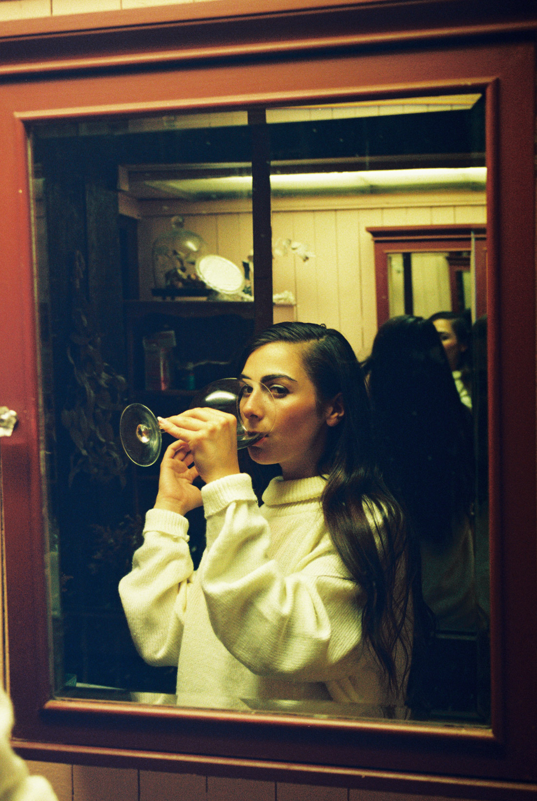 Cara drinking wine in the bathroom