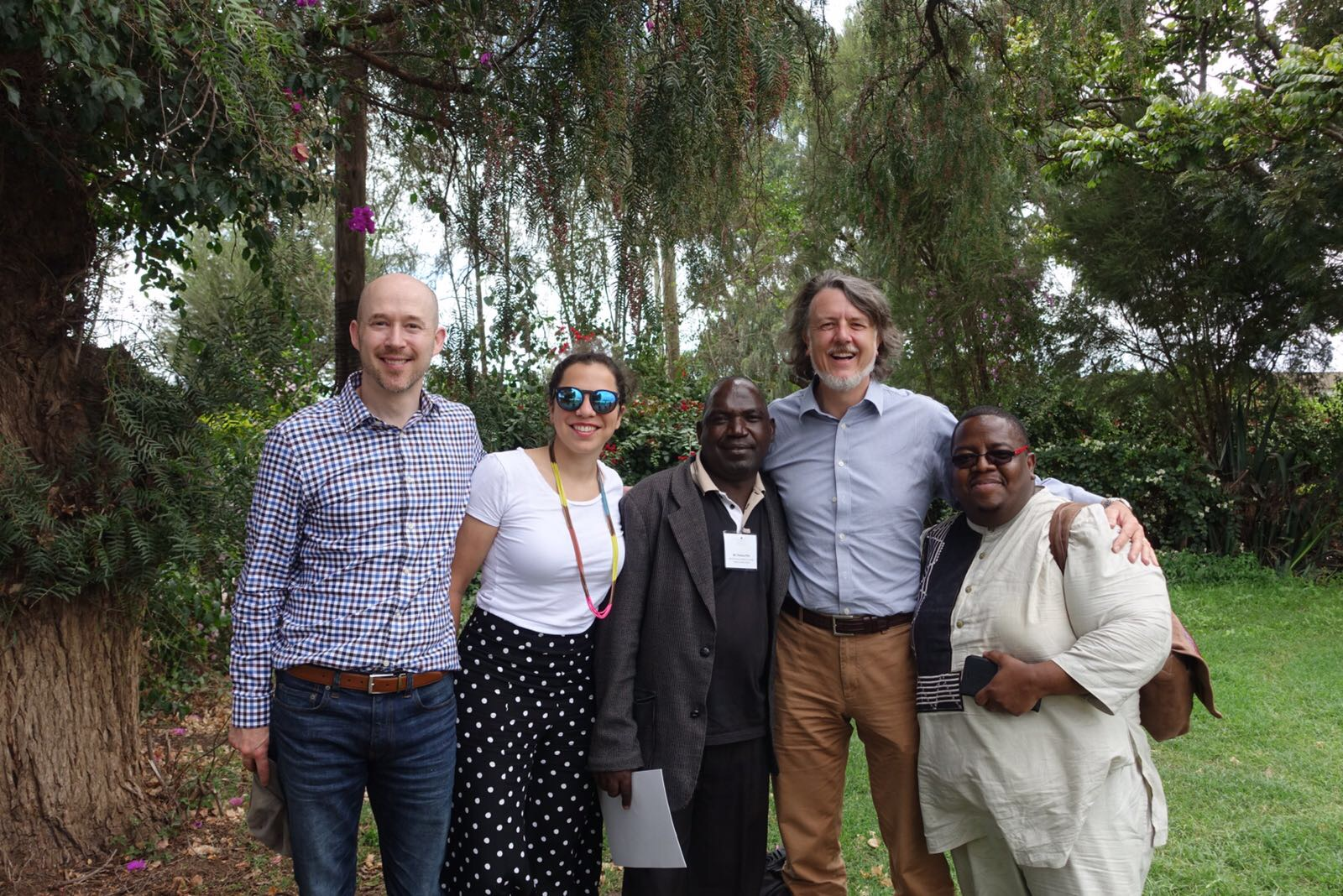Thomas Kisimbi (far right) led AMP Health team members on a field visit in Kenya to see how the community health system operates firsthand.