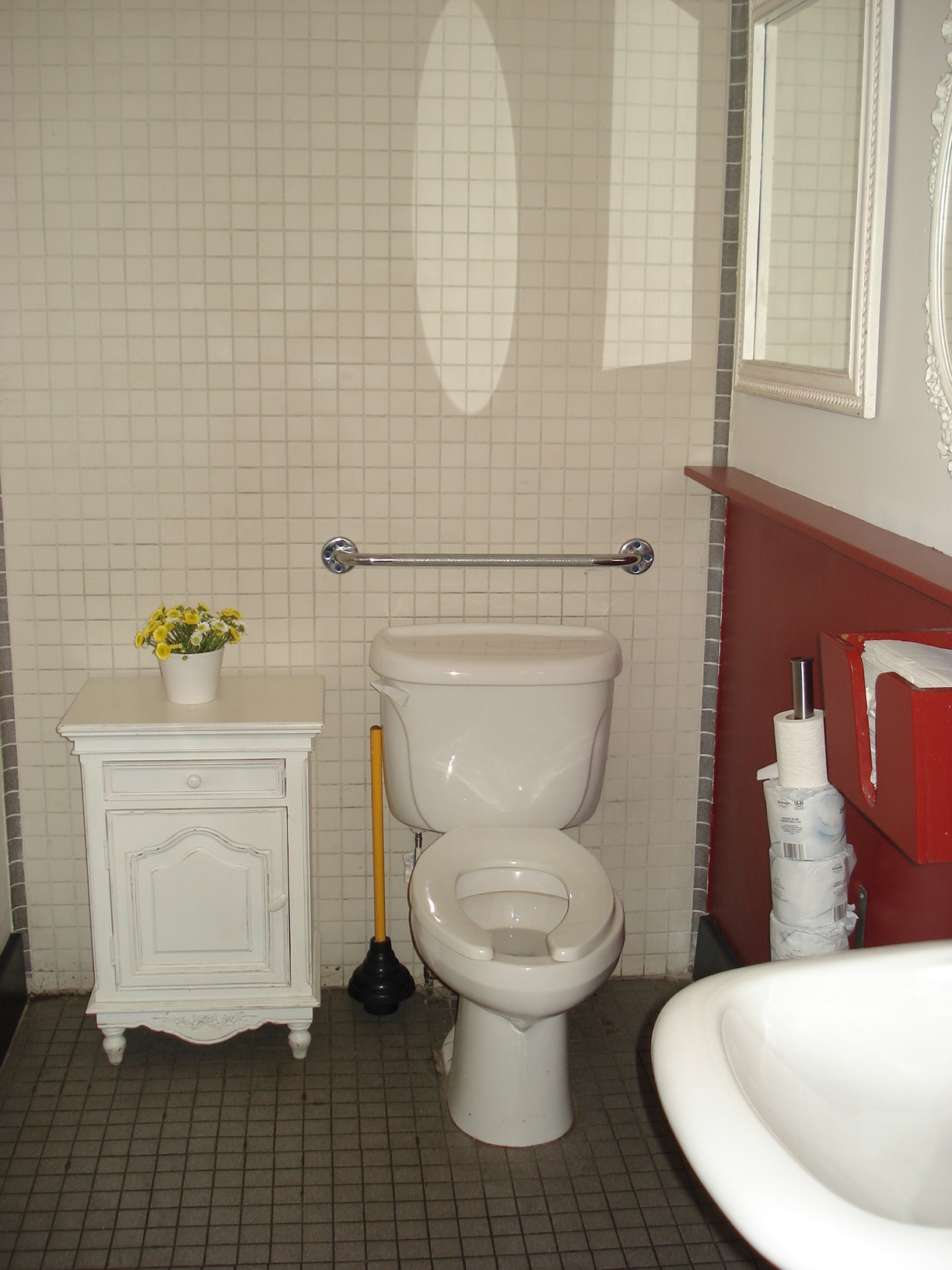 Picture of accessible washroom. Grab bar above toilet tank.