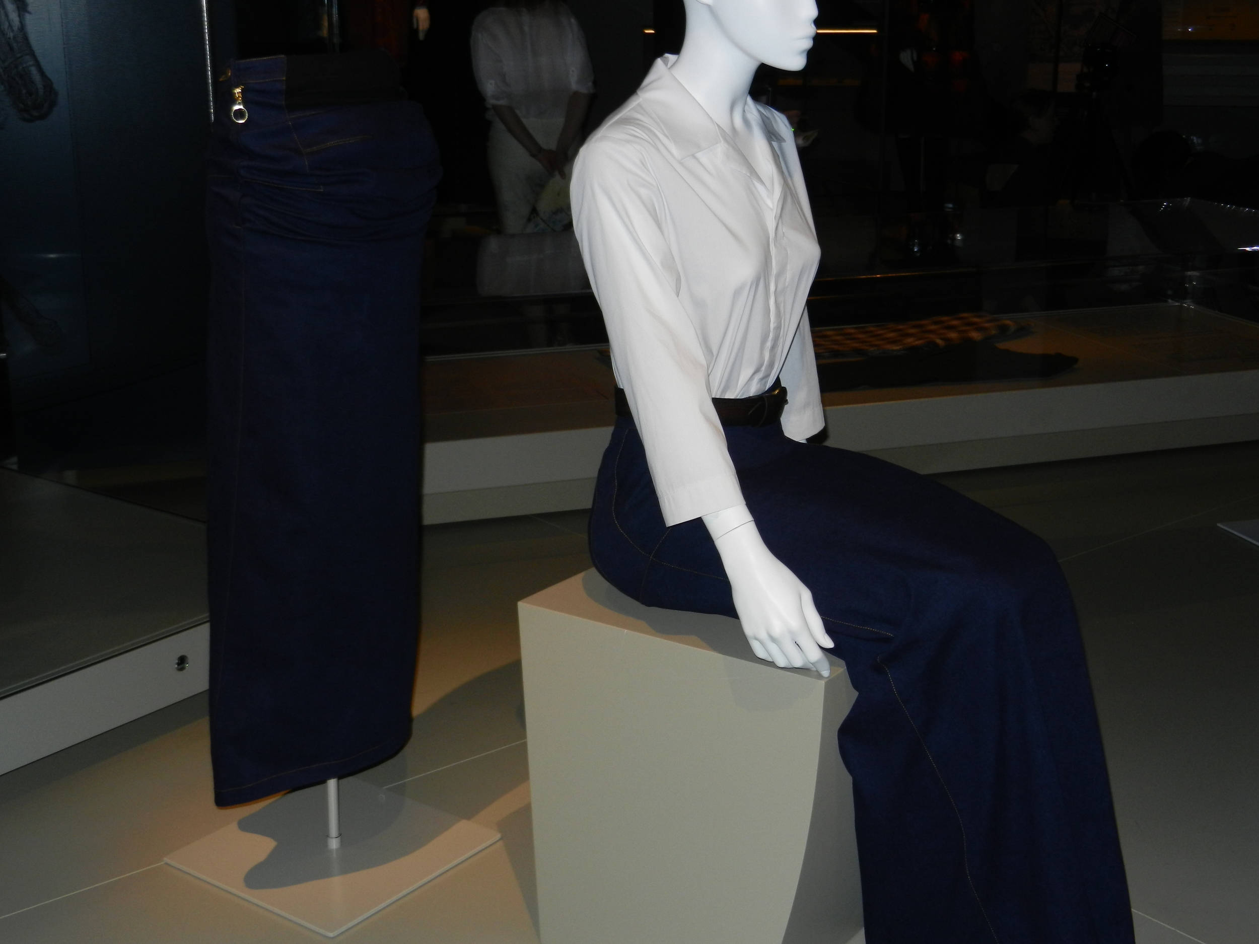 Picture of mannequin wearing blue skirt sitting down.