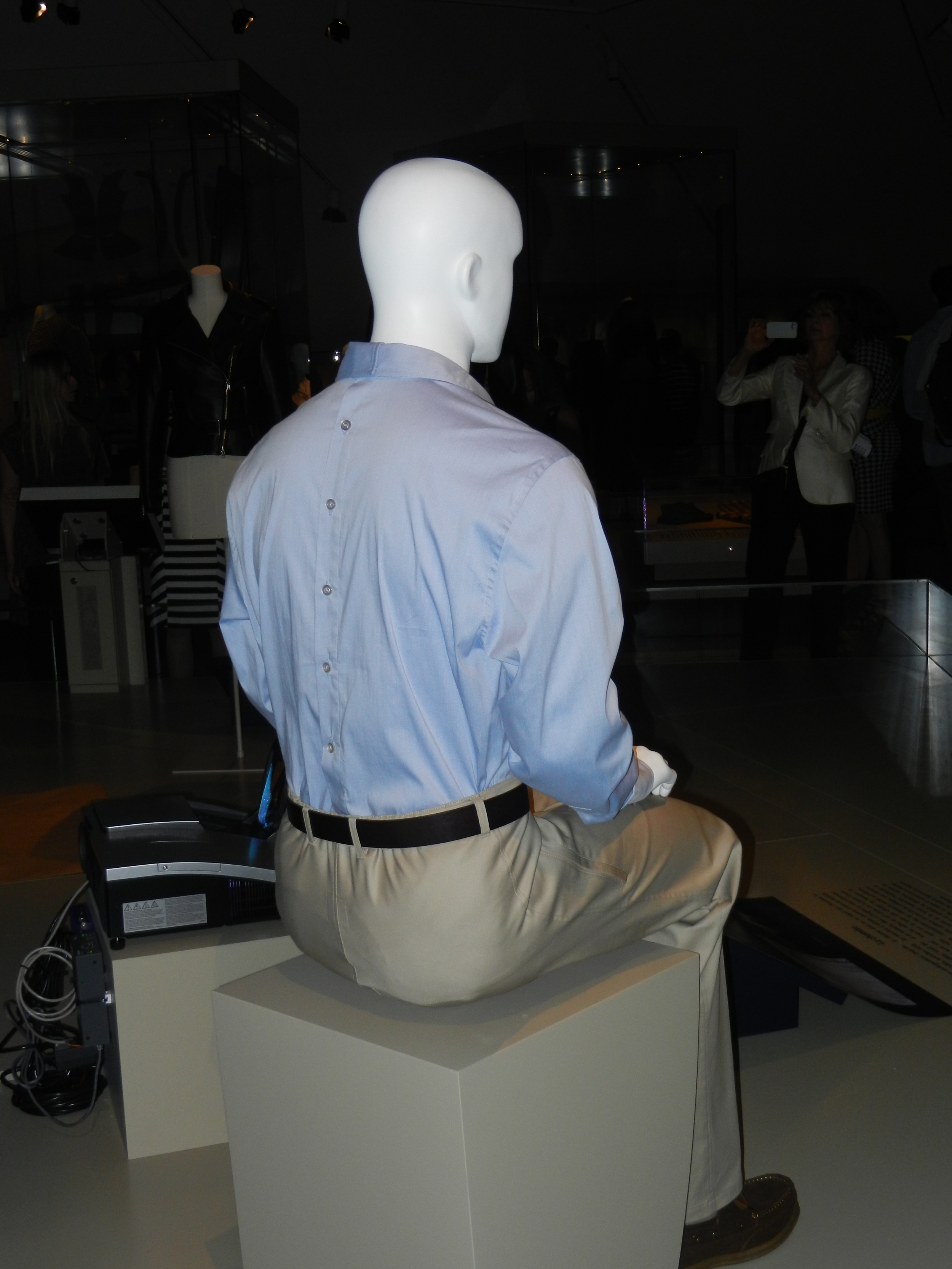 Picture of mannequin in blue shirt sitting down.