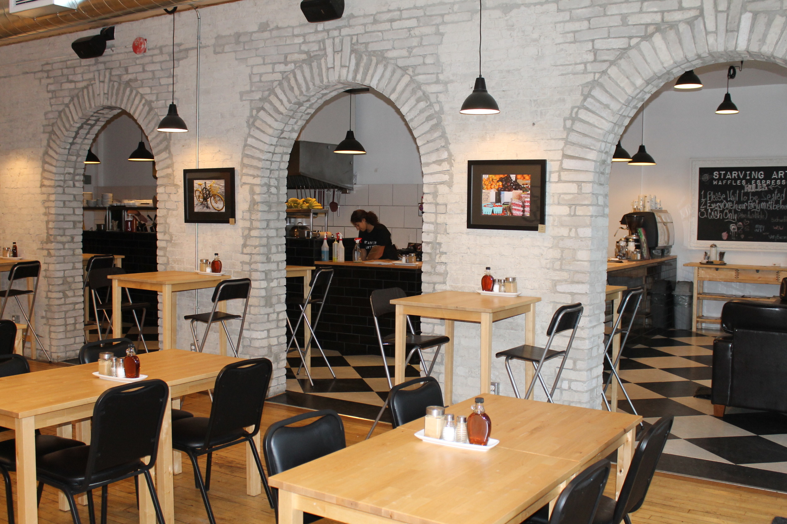 Picture of accessible interior. Wooden tables, black chairs.