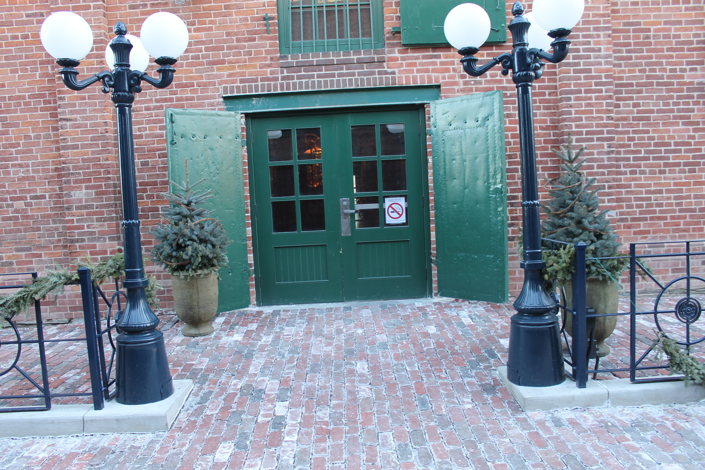 Picture of accessible entrance. Green door with 2 lamp posts.