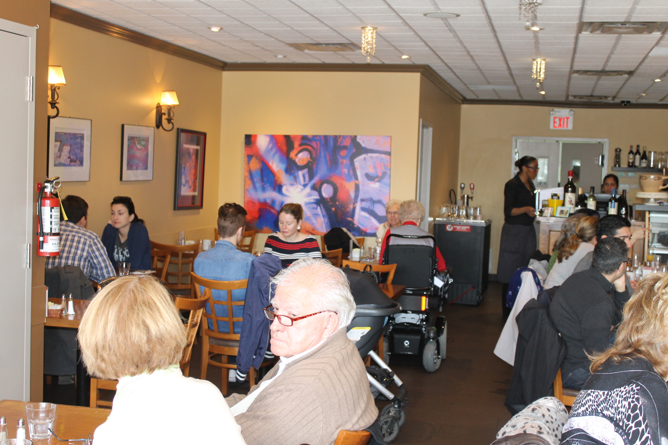 Picture of accessible interior of restaurant. Woman in power wheelchair at one table.