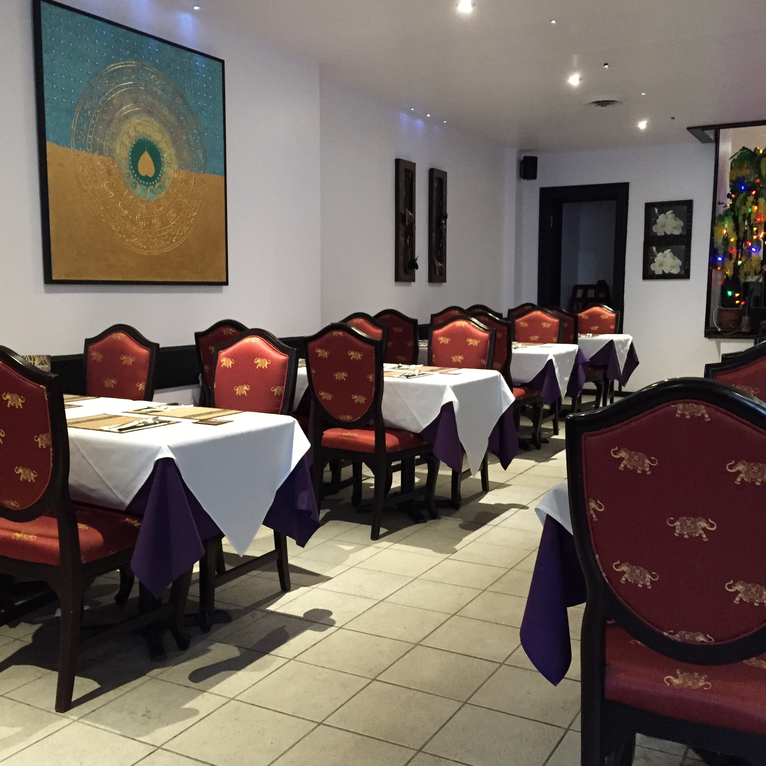 Picture of interior of restaurant. White tablecloths, red chairs.
