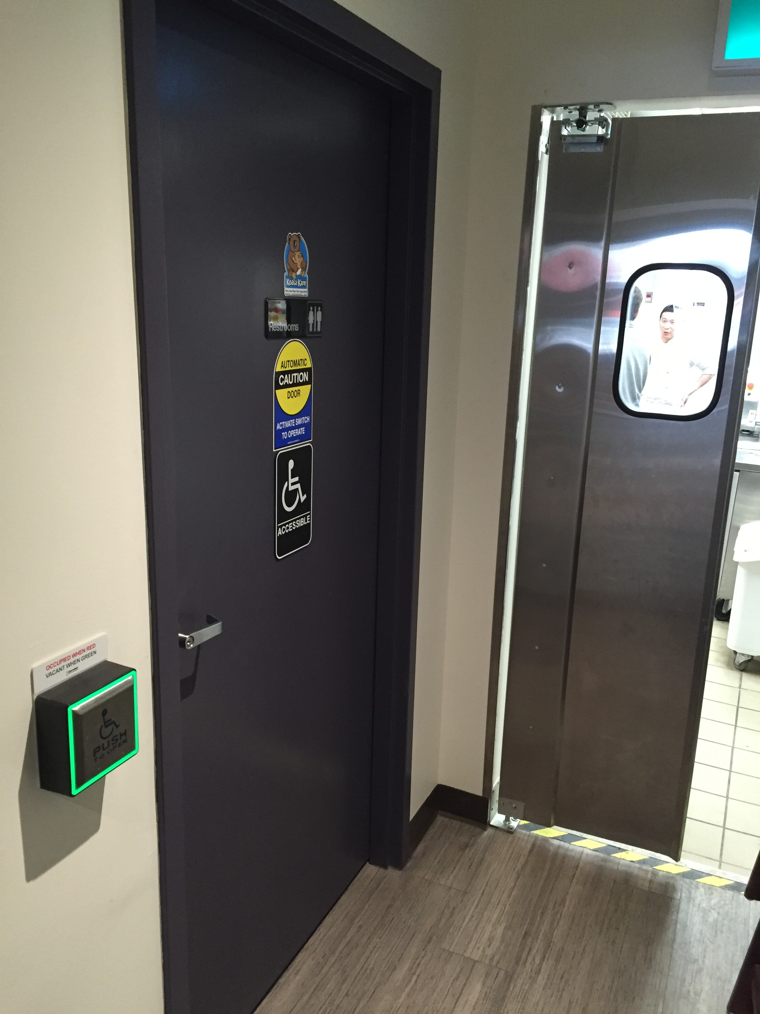 Picture of entrance of accessible washroom. Automatic push button to the left.