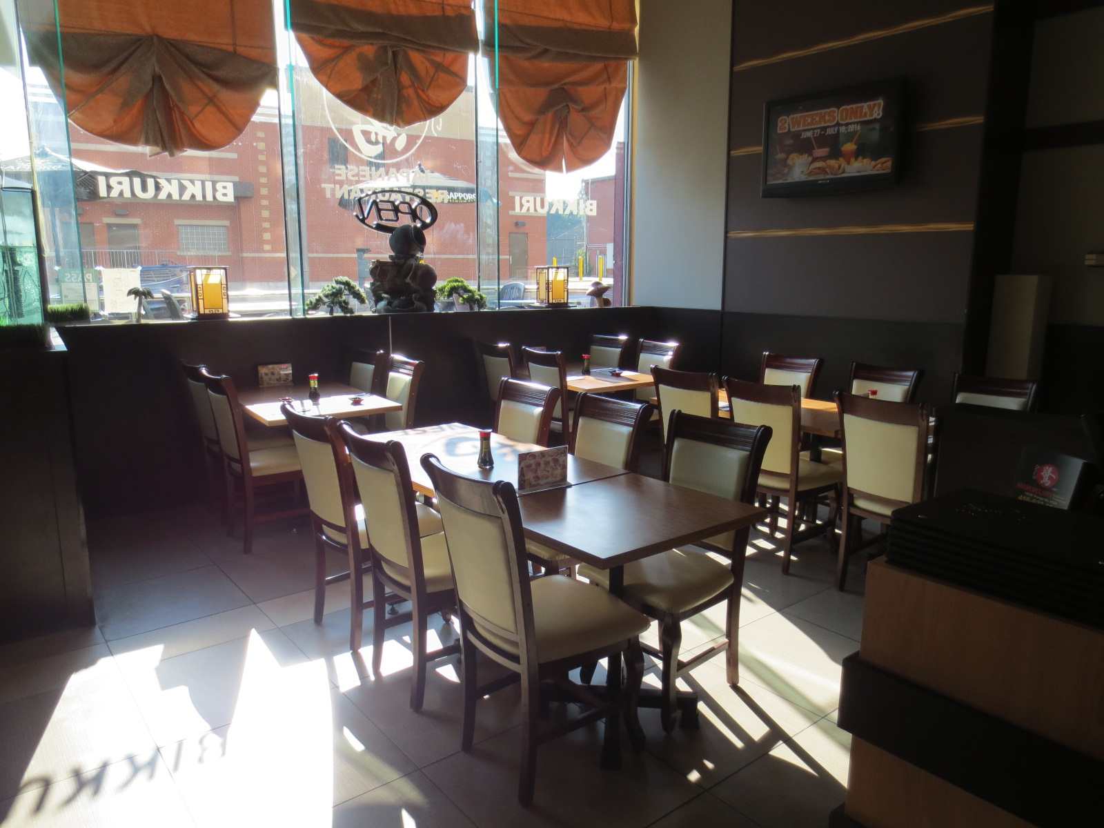 Picture of main dining area in front of restaurant. Standard height tables shown.