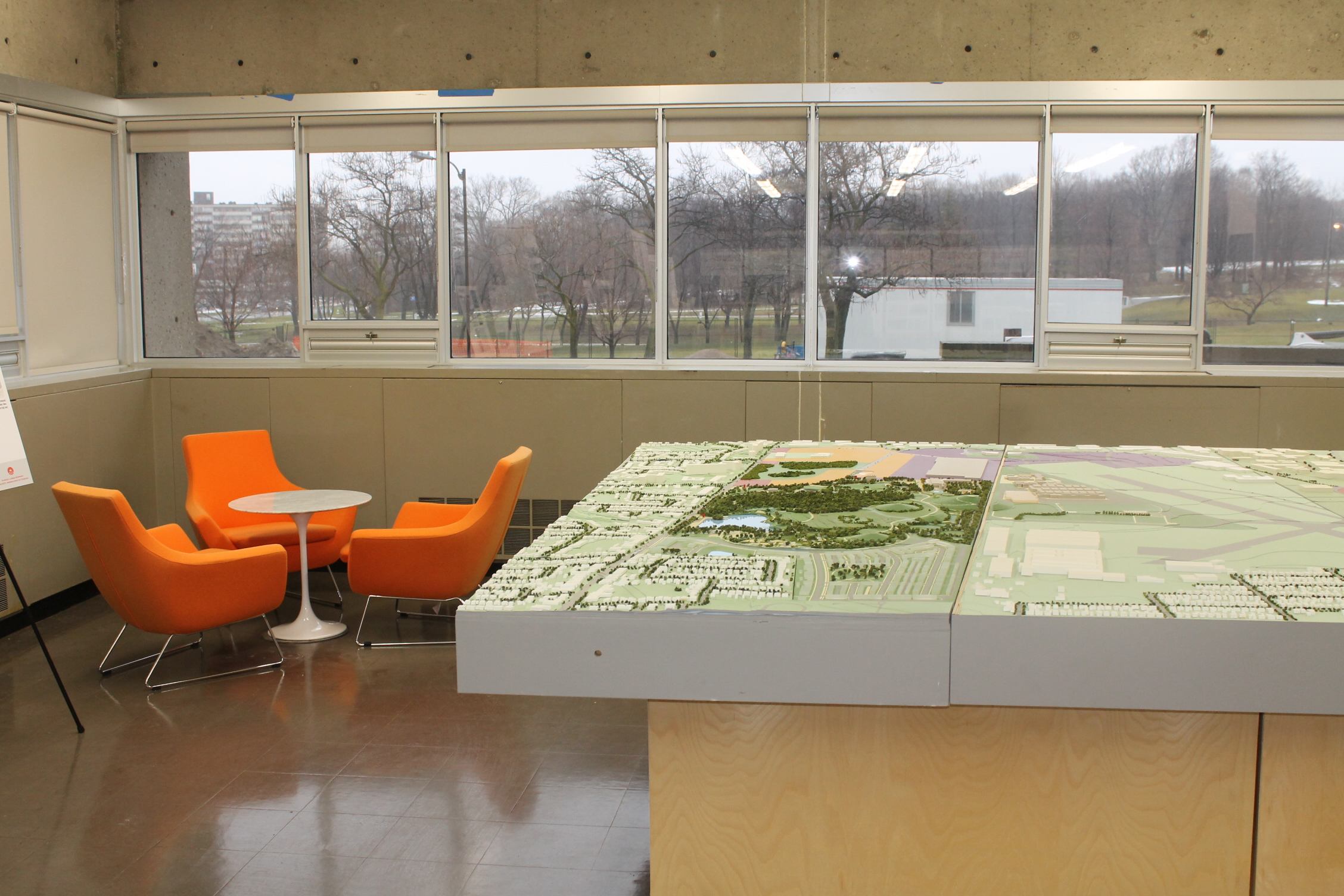 Picture of interior of the Downsview Hub. Small table with orange chairs displayed