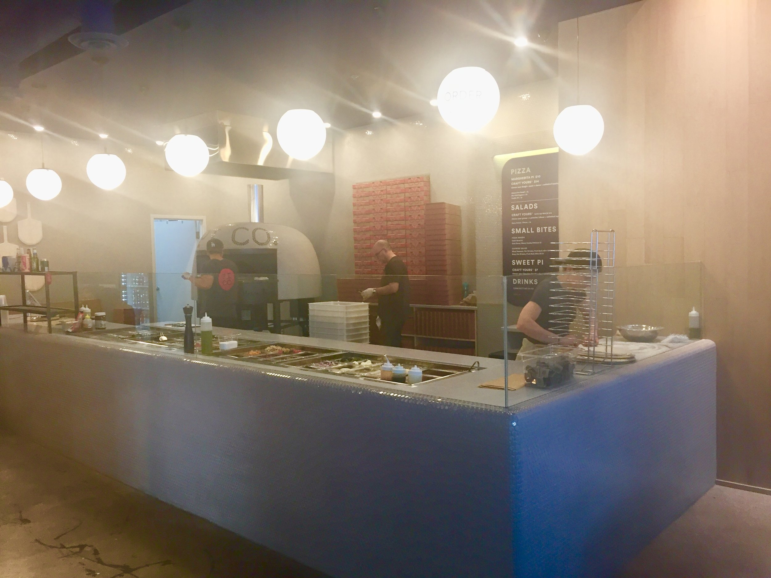 Picture of chefs cooking behind the counter at Pi Co.