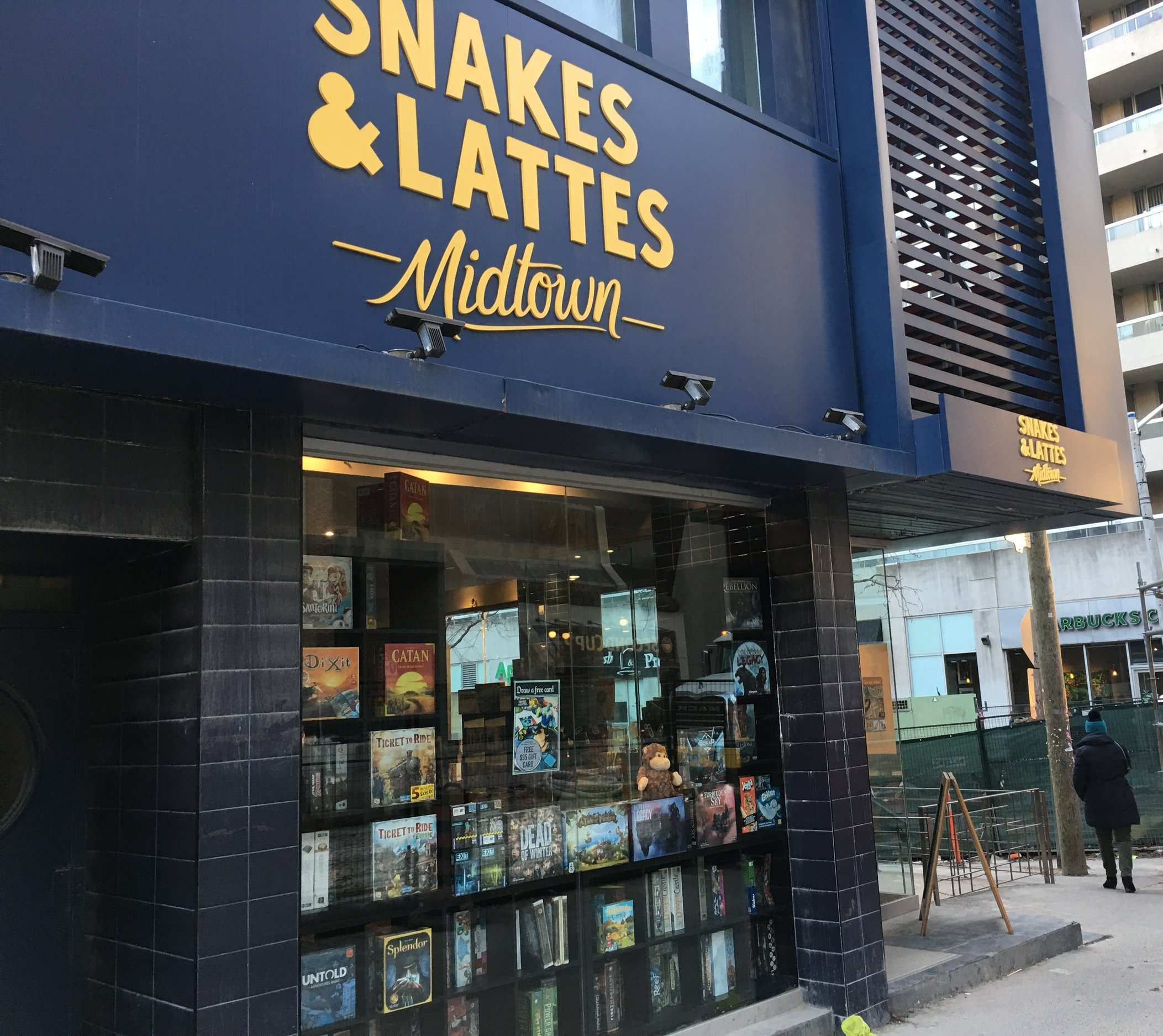 Picture of entrance of Snakes & Lattes with one step leading to door
