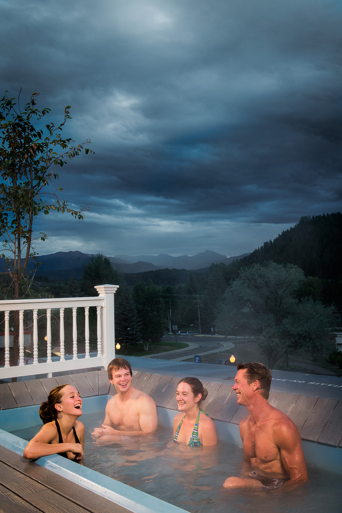 Advertising image of friends soaking in a rooftop hot spring tub in Pagosa Springs, CO