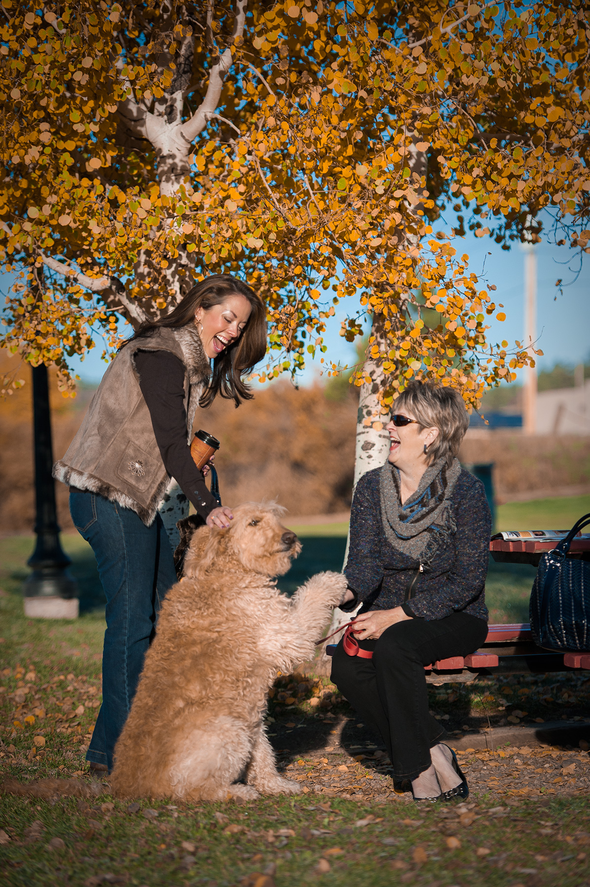 Lifestyle image of two woman and a dog in a park