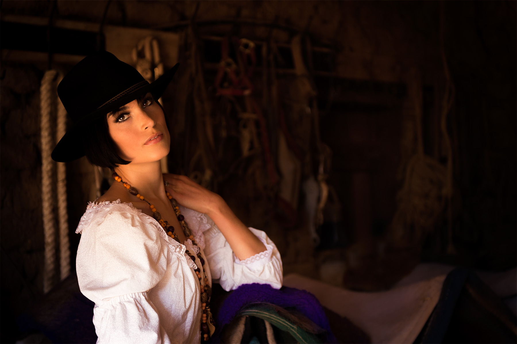 Fashion photo with a cowgirl inside a tack room on a ranch near the Mexico/Arizona border
