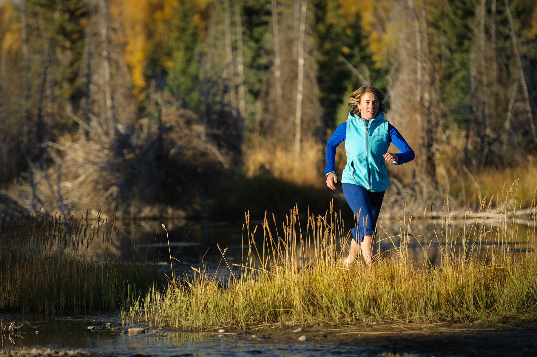 A female athlete runs next to a lake near Jackson, WY