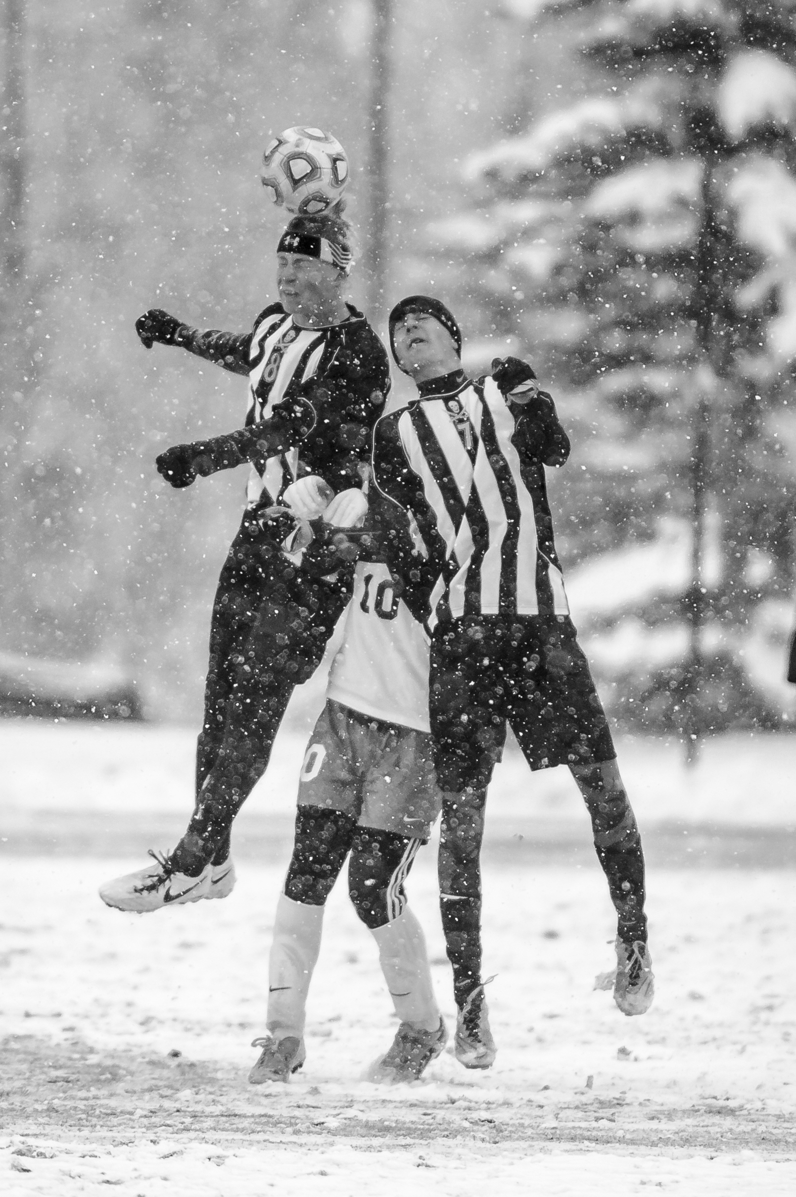 Players battle for a header through a heavy snowstorm during a playoff soccer game