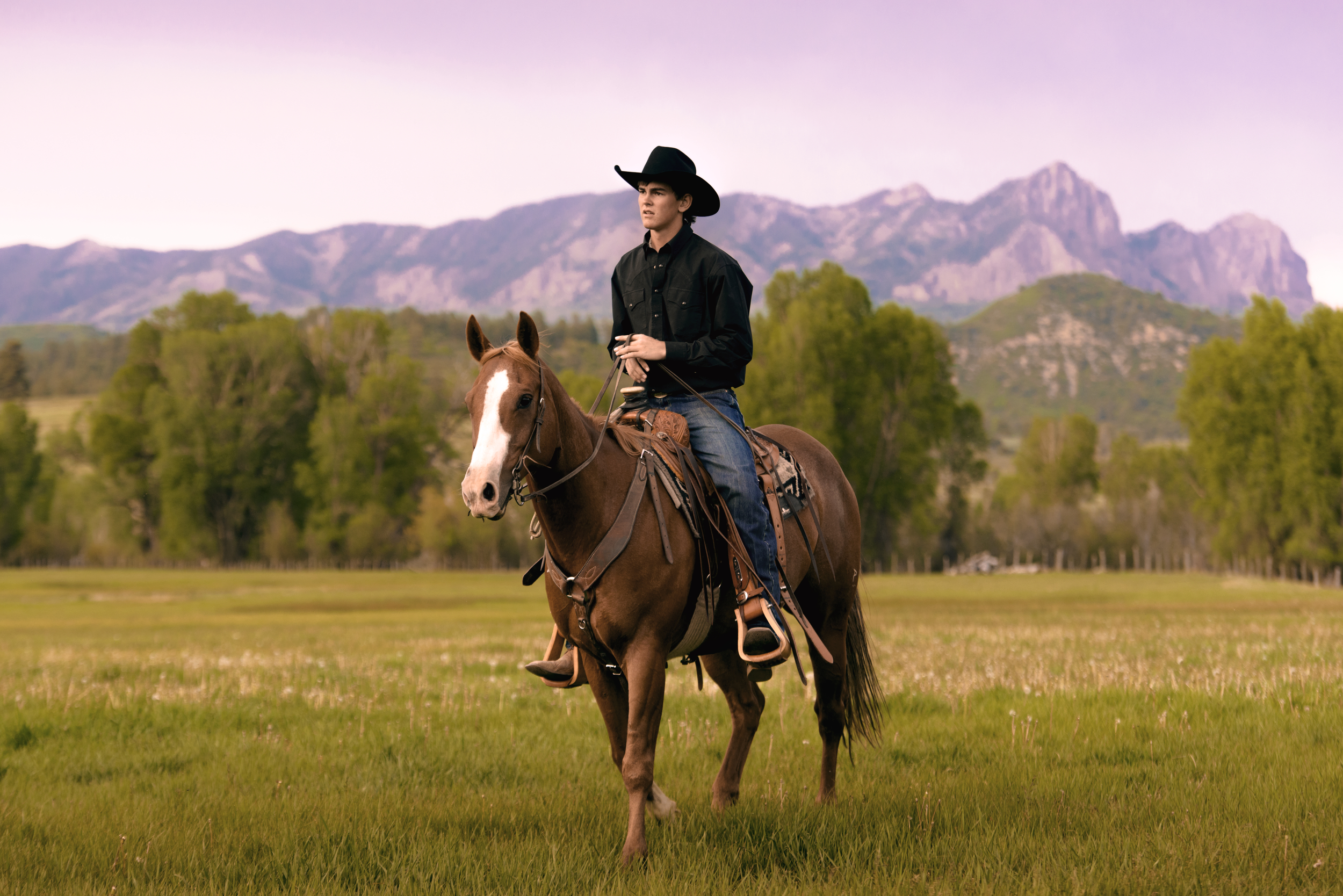 Cowboy riding a horse at sunset in the Southern San Juan mountains of Colorado