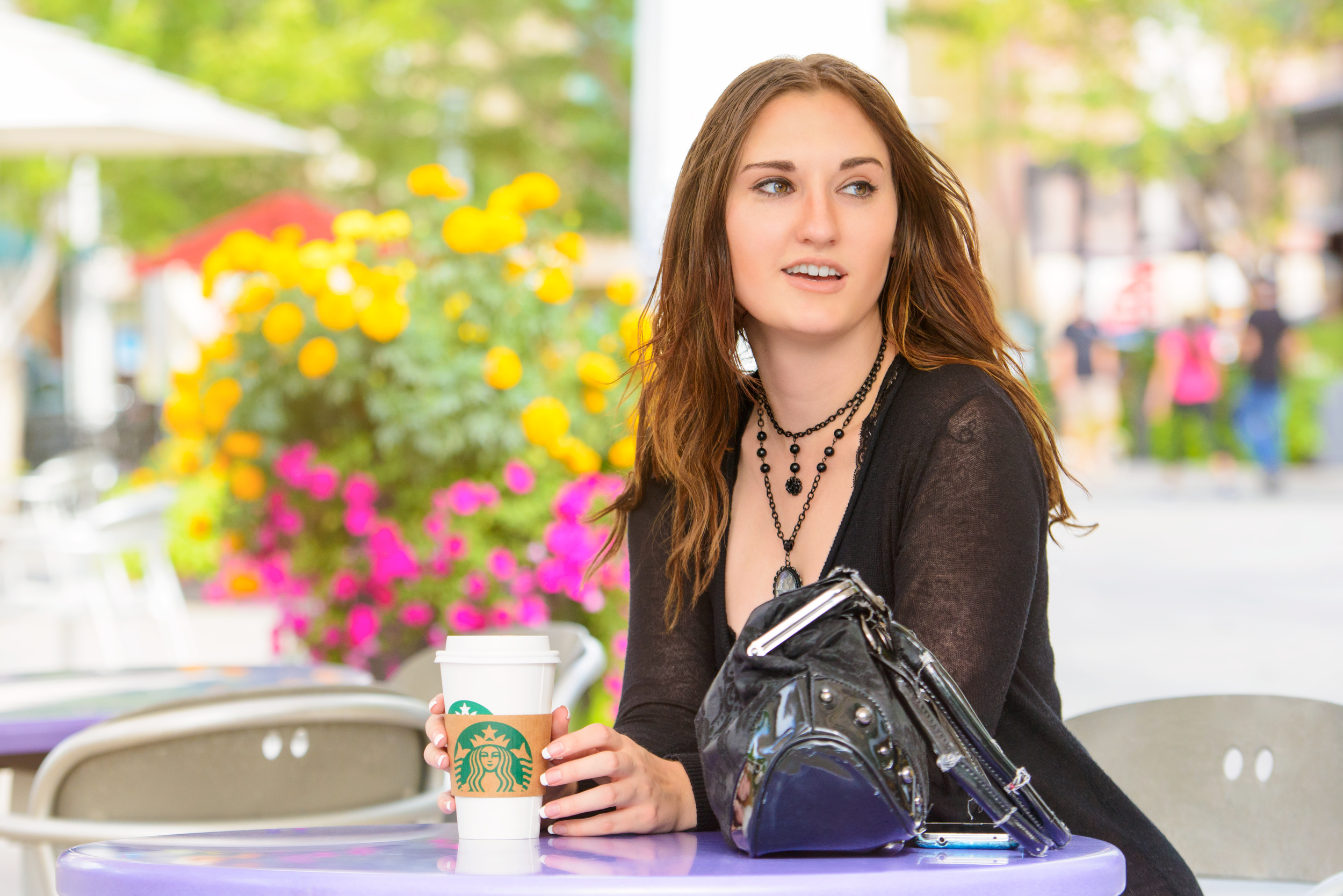 Adverting lifestlye image of a young woman with Starbucks on plaza patio