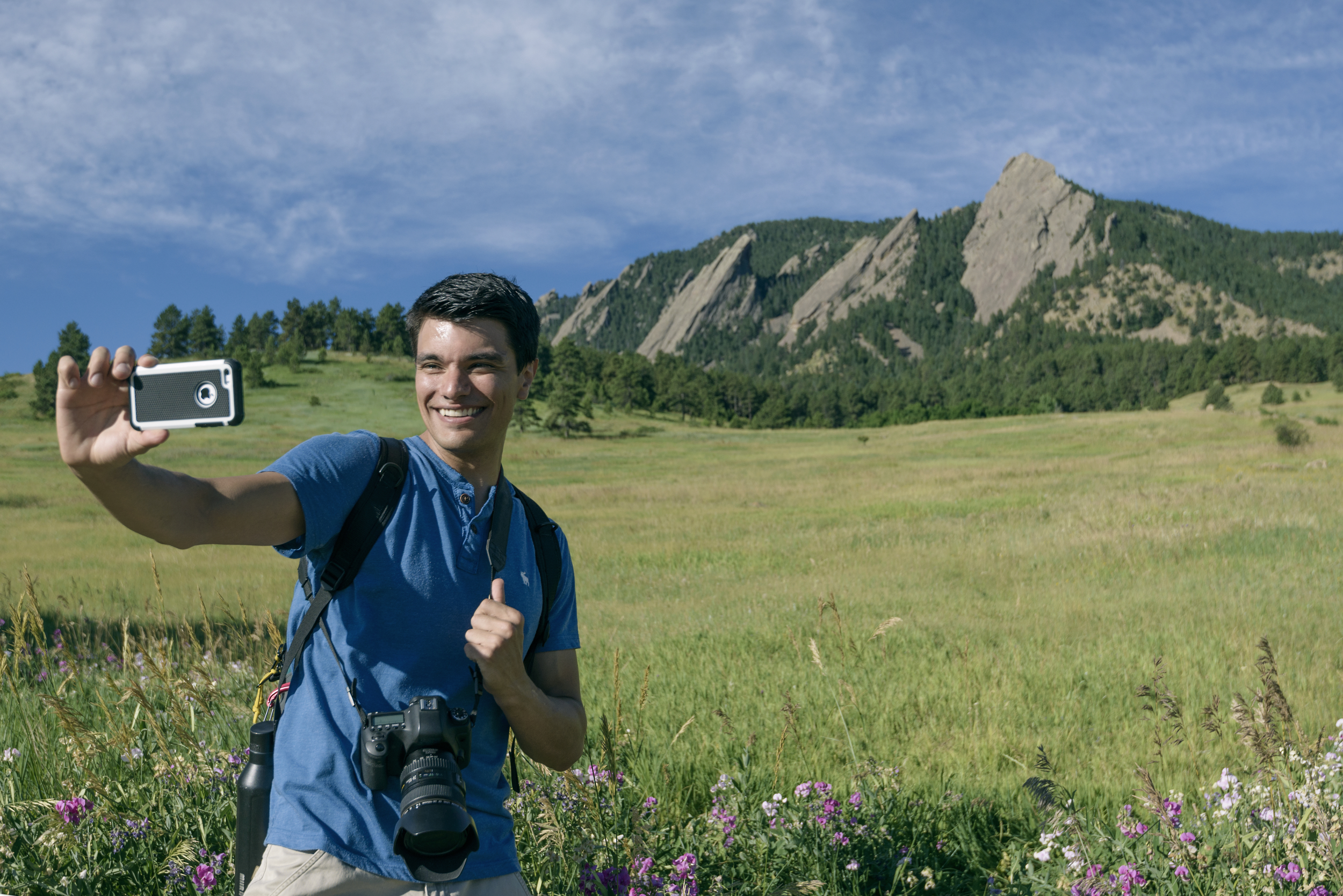 Lifestyle product photo of male taking an iPhone selfie and hiking near the Flat Irons outside of Boulder, CO.