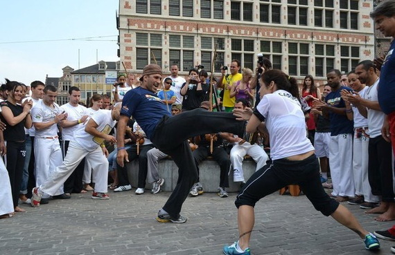 Mestre Sabiá playing with Professora Pimentinha at an outdoor roda in Belgium he organized. As you can see from all the onlookers behind the players, Capoeira always draws a crowd. To see more  click here.