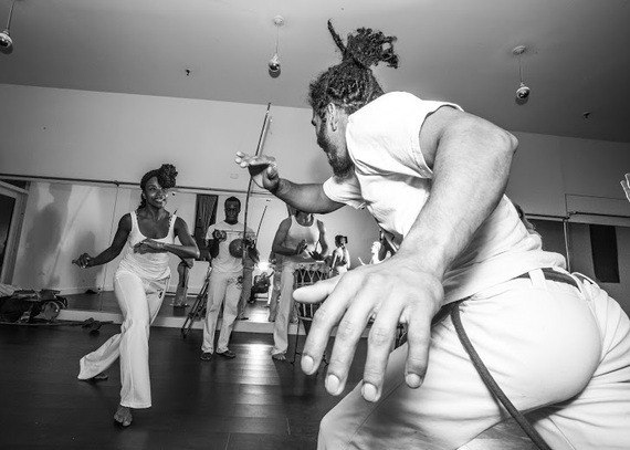 Students spend years learning how to do the first, basic movement of Capoeira, which is the Ginga (or swing), which Pena can be seen teaching a white chord (or beginner) how to do above. (Photo by  Ace Murray / Brooklyn Juice Photography .)