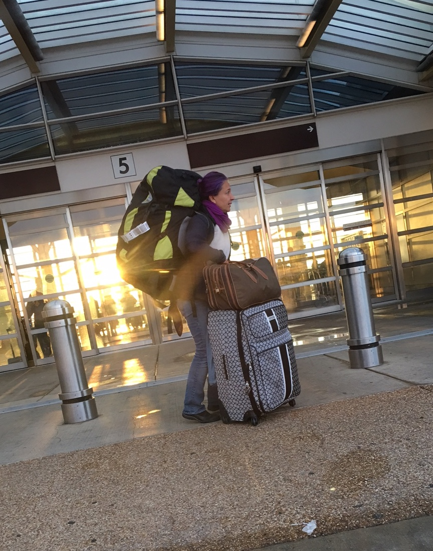 My great niece, Asia, snuck a shot of me trying to figure out what was going on. Far too early to be leaving with all of this luggage for Europe. Especially when American Airlines had only ONE check-in open and it was outside for some reason.