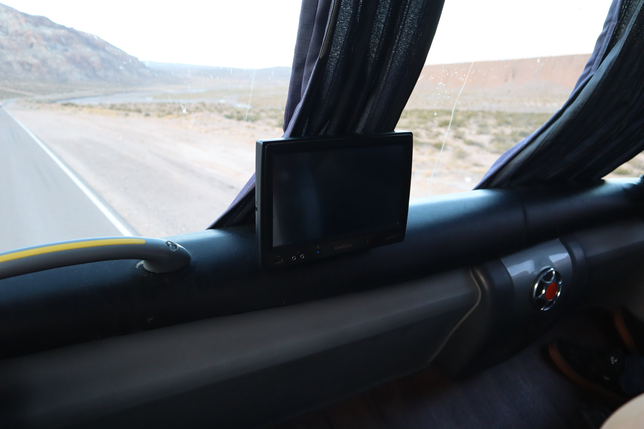 The view out of the front of the bus as well as a tv screen.