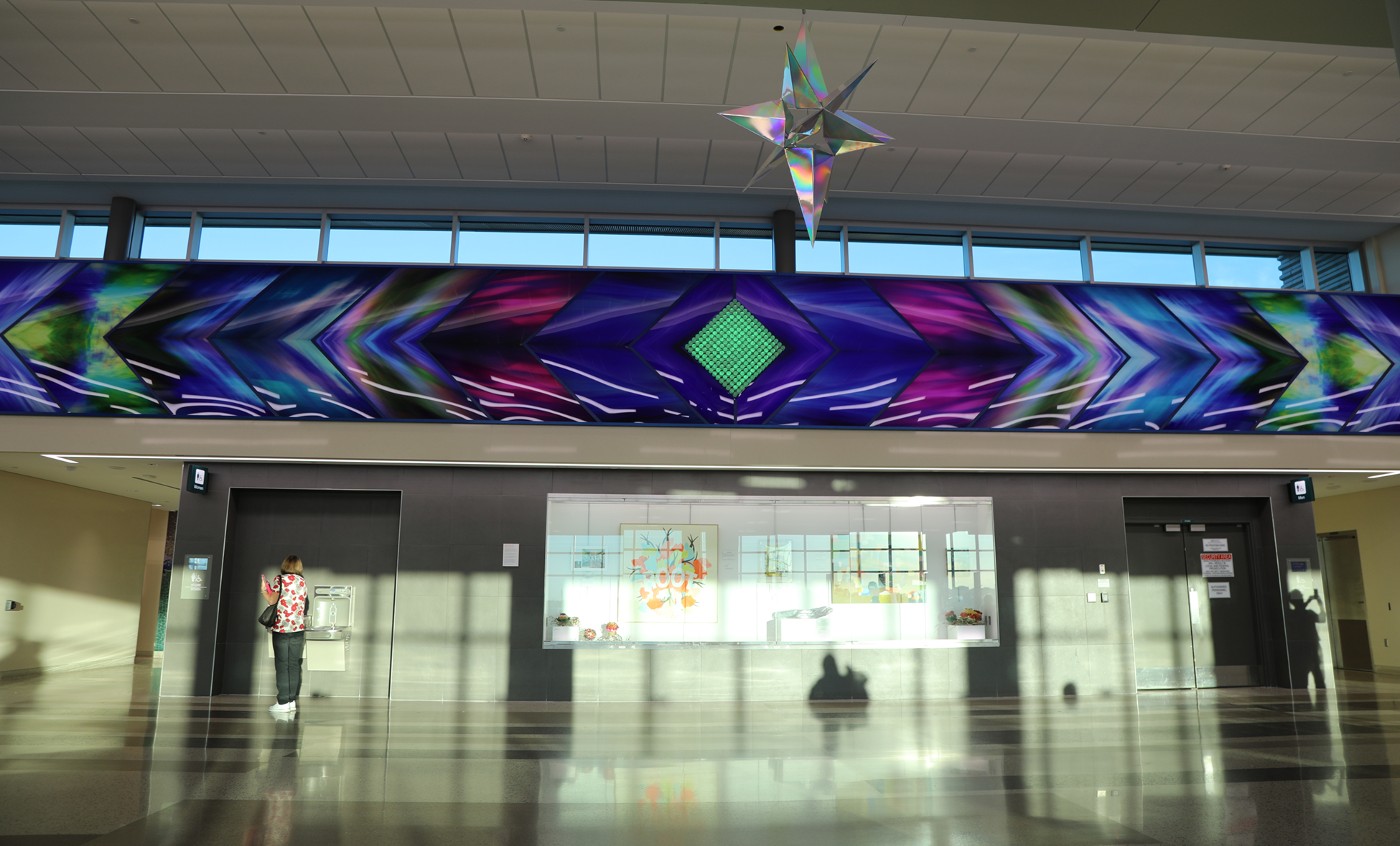 Aurora Borealis, brings the colors of the Northern Lights to life in the airport. The Aurora Borealis wall is 60 feet long by 6 feet tall. In the very middle of this sixty-foot long series of images is a rainbow diamond made of clear acrylic rods and lit with LED color lights that go through the colors of the rainbow.