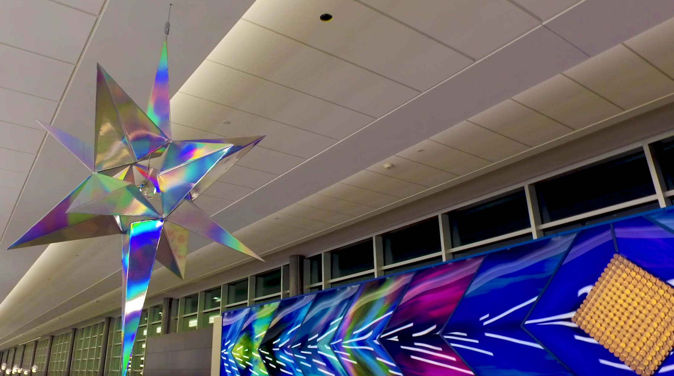 "This artwork is based on the Minnesota state motto, ""  L'Etoile du Nord"" (Star of the North) is based on the Minnesota State Motto that was first adopted in 1861 and is on our state seal. L'Etoile du Nord is 6 feet tall, made of aluminum and covered with holographic rainbow vinyl.  Inside the star is a crystal prism that is lit so tiny light rainbows show on the ground below the star.      L'Etoile du Nord uses rainbows to both be visually beautiful, but also to impart the meaning that anybody of any race, creed, nationality or sexual orientation are welcome in Minnesota,."