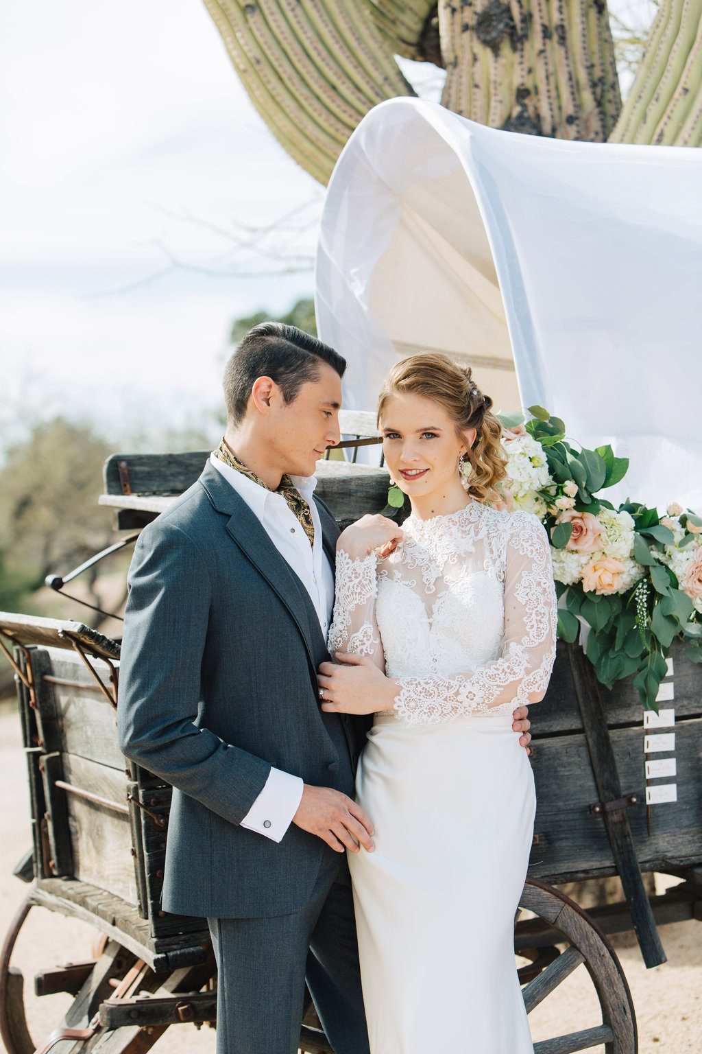 Bride, Groom, Phoenix Scottsdale Arizona Wedding Planner, Bridal gown, lace bridal gown, sleeved bridal gown, Groom attire, grey suite, southwest, ascot, groomsmen attire, Orchids, blush, peach, southwest, elegant, flowers, roses, rustic, western,  escort cards, wedding wagon