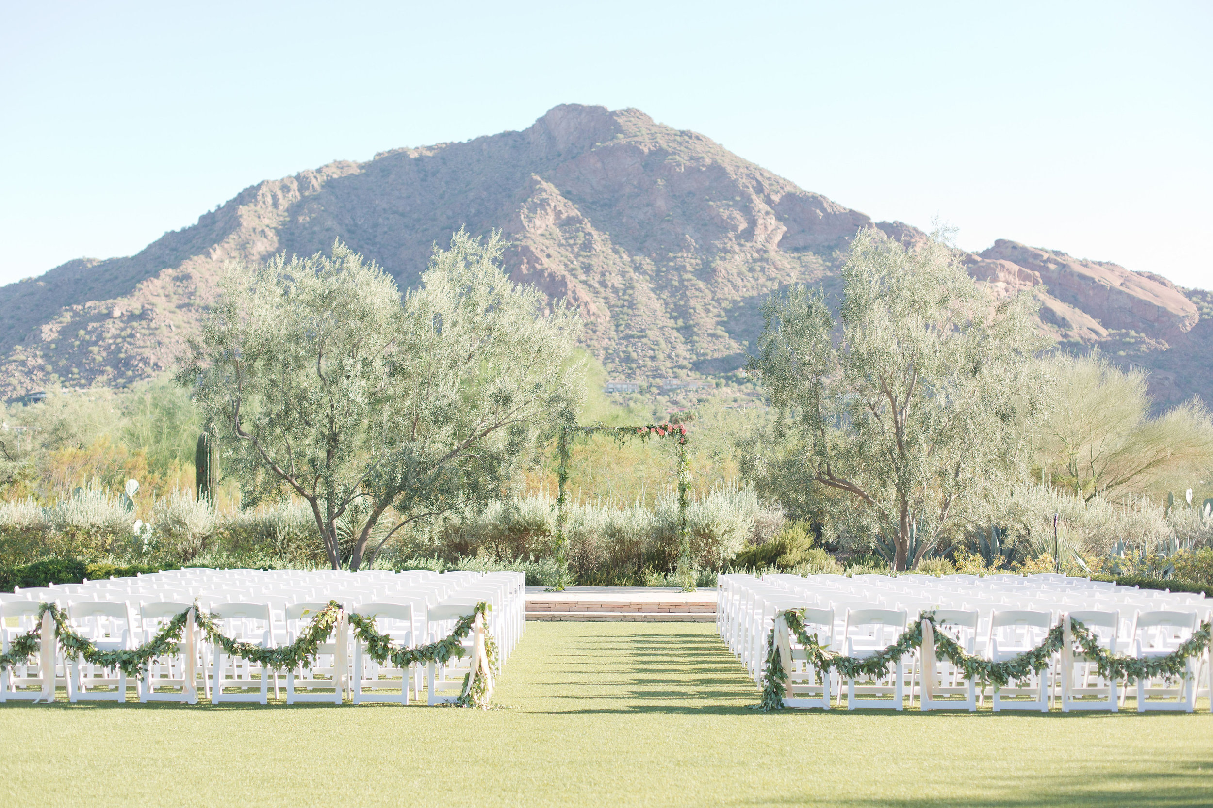 peach and mint wedding, blush and green wedding, Arizona Phoenix Scottsdale wedding planner, ceremony, greenery on alter, greenery on chair backs, peach blush wedding flowers, camelback mountain ceremony view, desert wedding