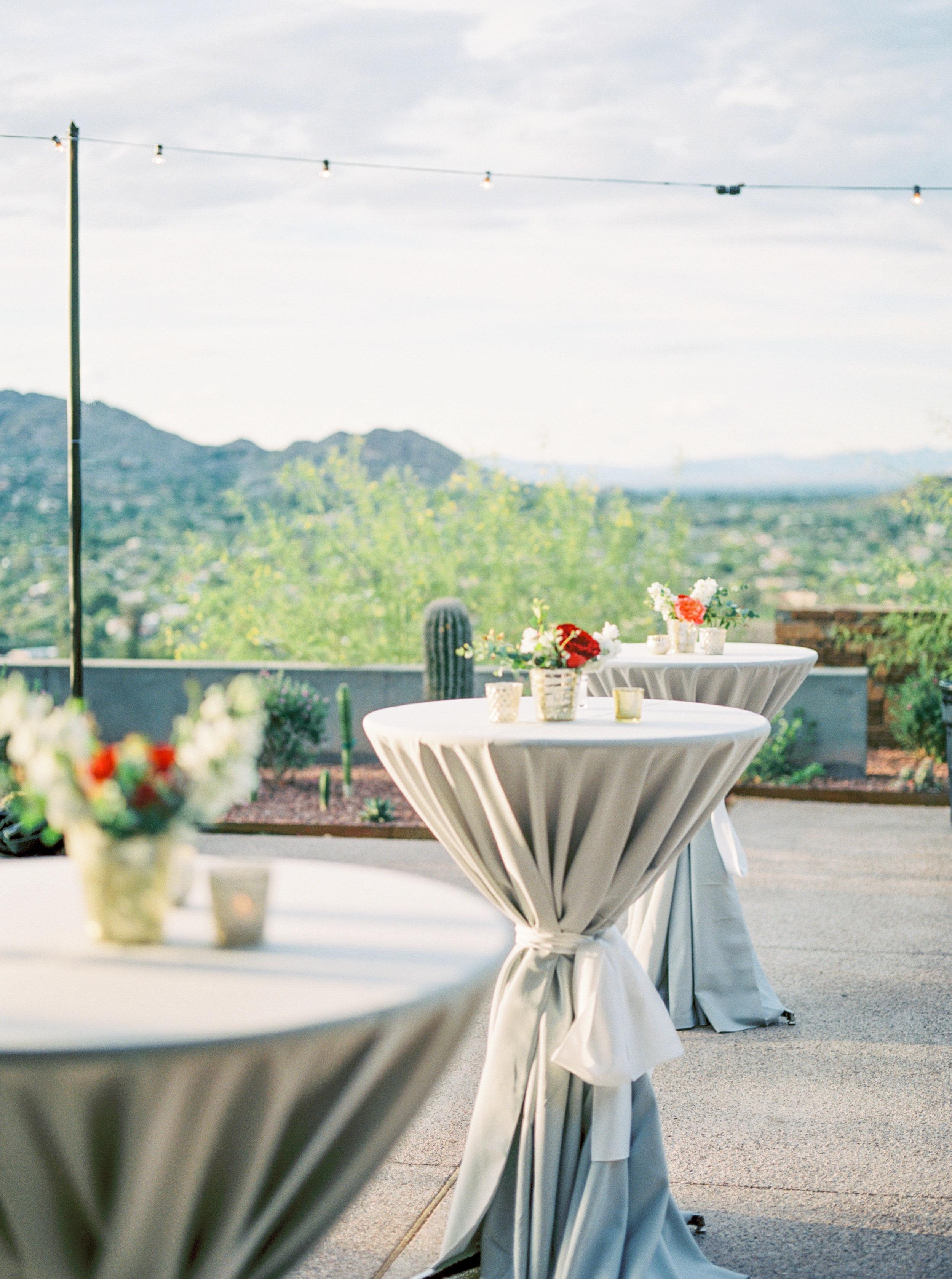 wedding cocktail hour, cocktail tables, gray linens, cacti decor, string lights, garden wedding flowers, mercury glass votive candles, orange wedding flowers, red wedding flowers, ivory wedding flowers