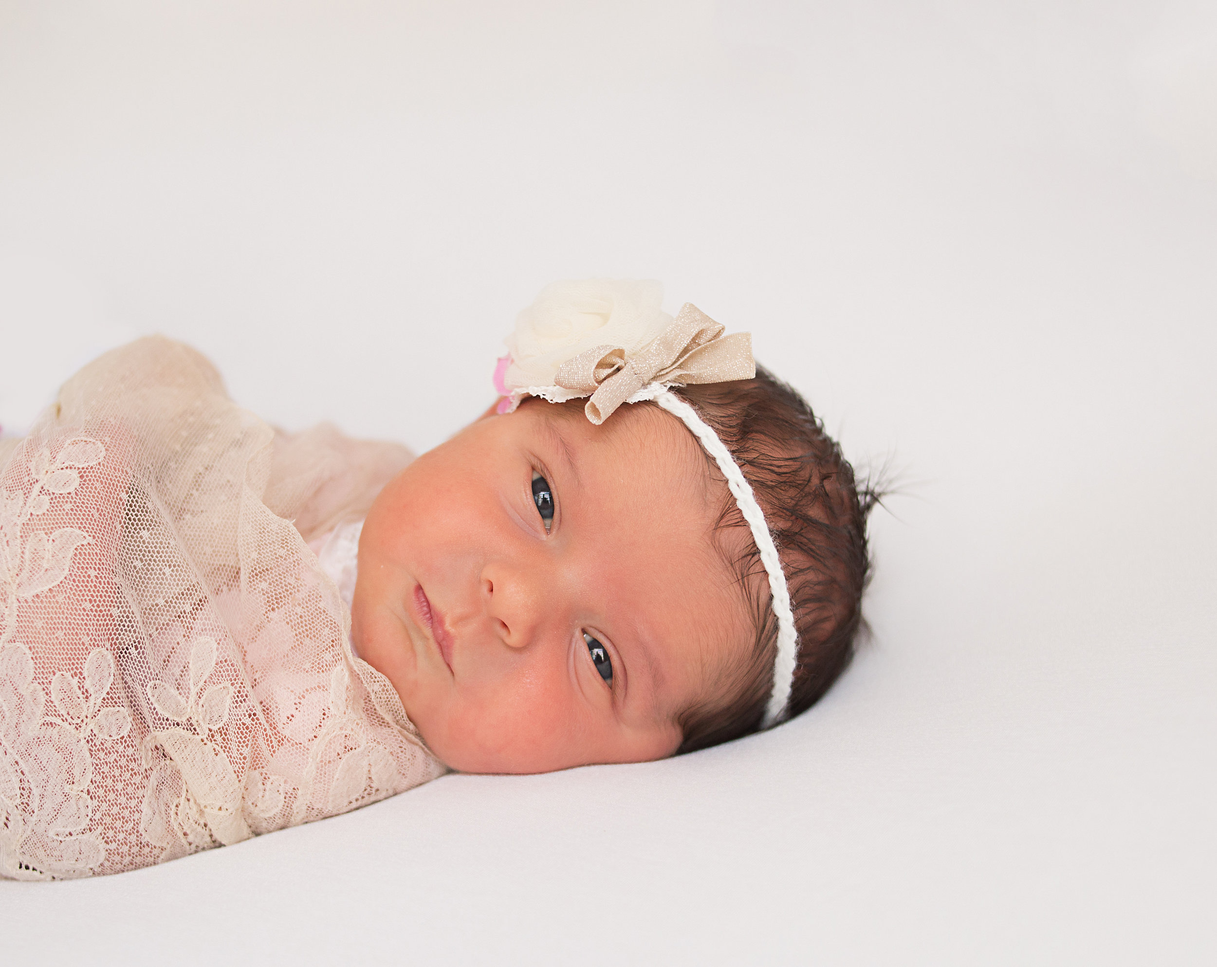 orange county newborn looking at the camera during her photography session