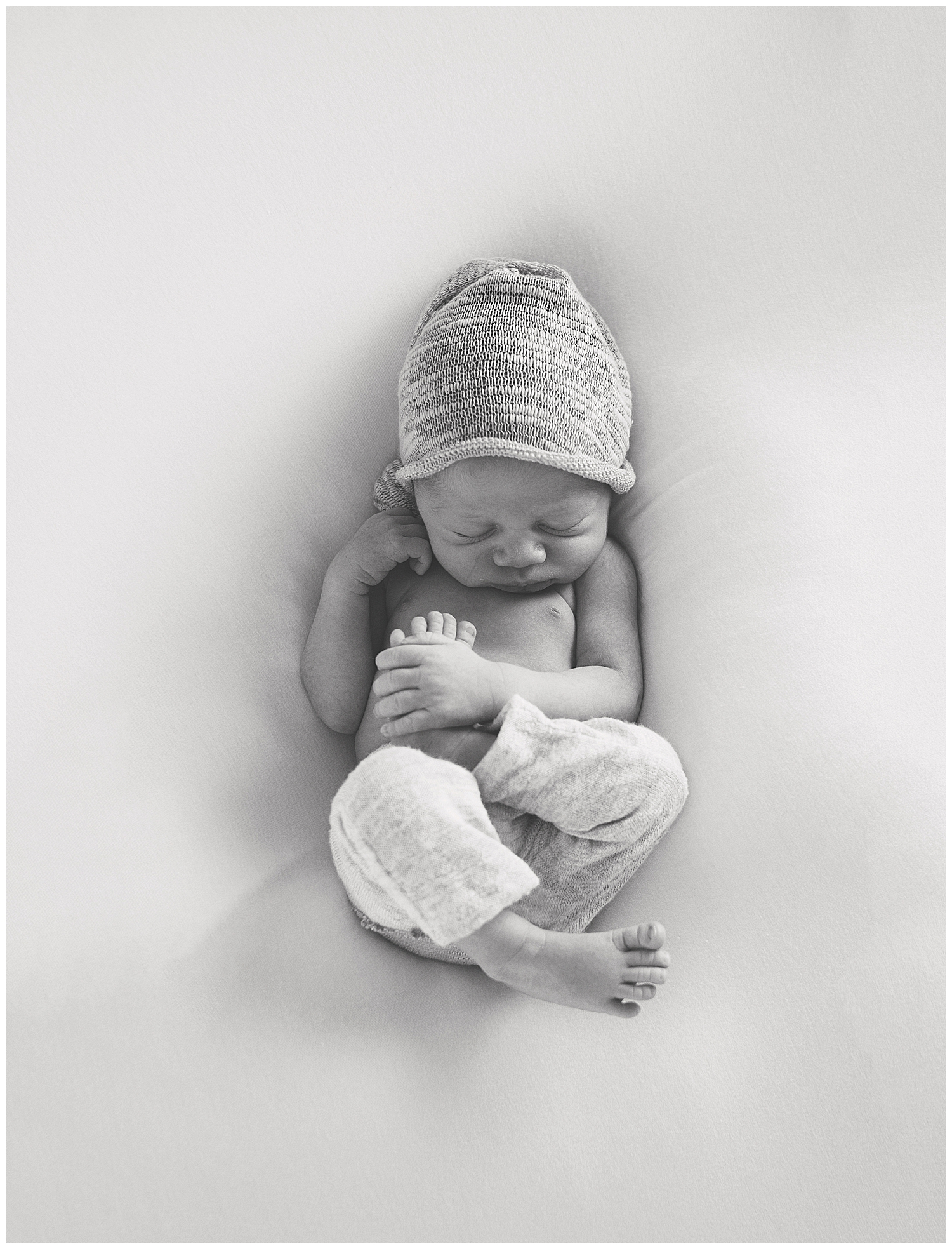 orange county newborn cuddled up during his photography session