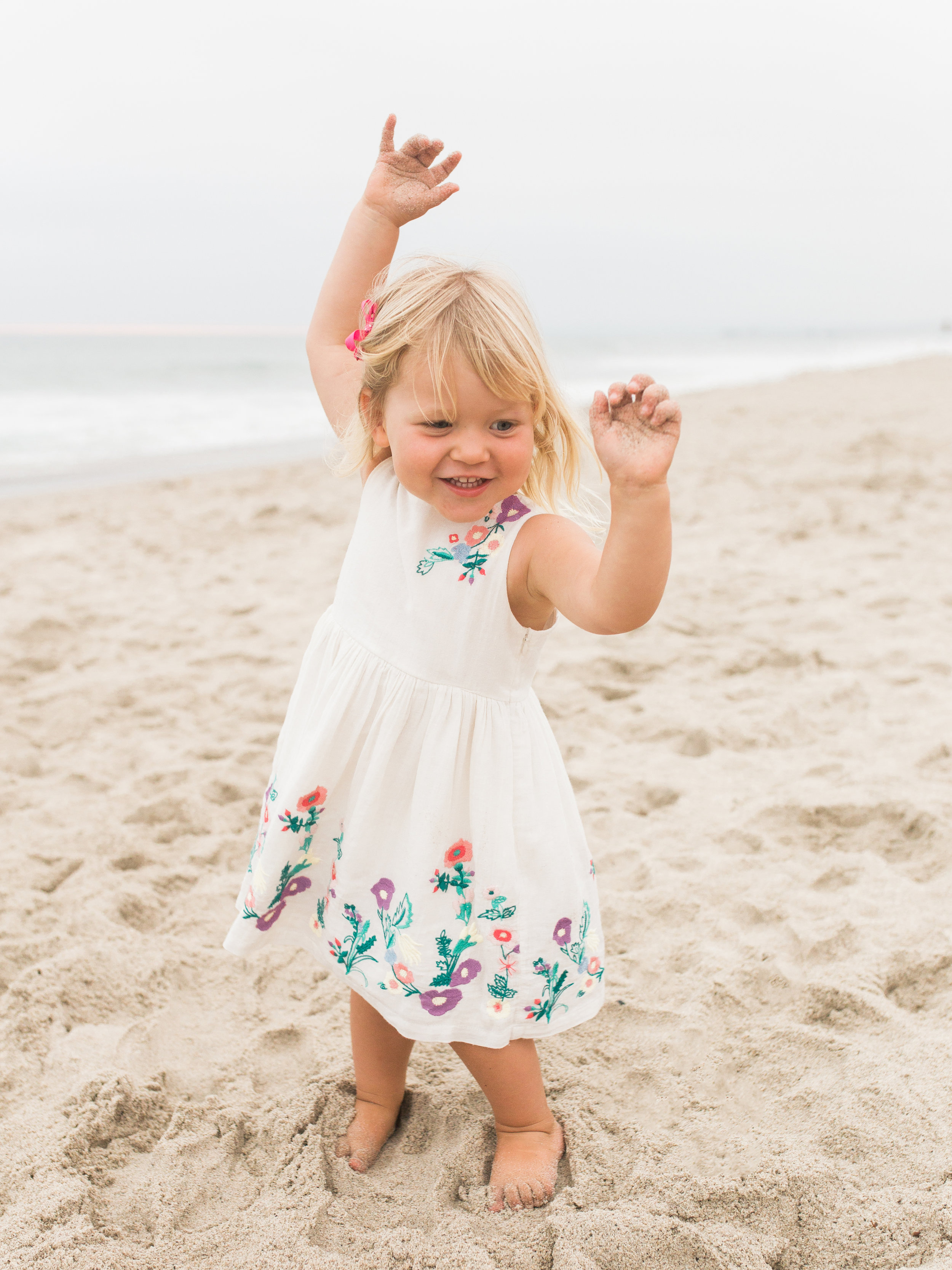 little girl dancing at her san clemente beach family photoshoot
