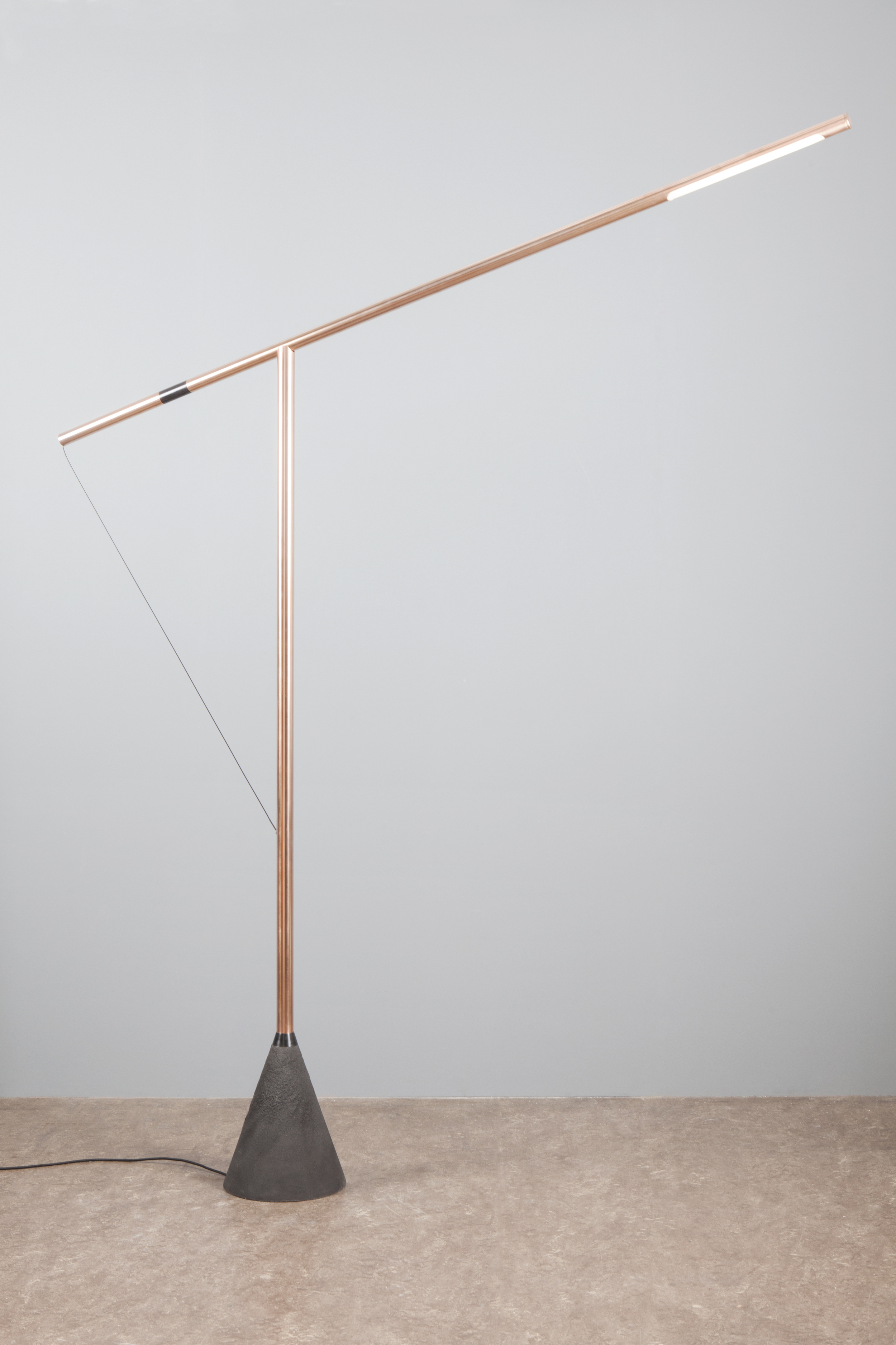 The lamp consists of two posts anchored by a single wire. A copper post containing an LED light source is balanced in a T-formation across another upright post. When the two posts touch, the circuit is completed and the LEDs turn on. The light can be adjusted by simply sliding the horizontal post to the desired position. By sliding the post on the non-conductive segment, the light is switched off.