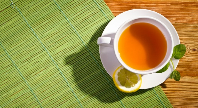 Hot tea with fresh leves and lemon on bamboo mat