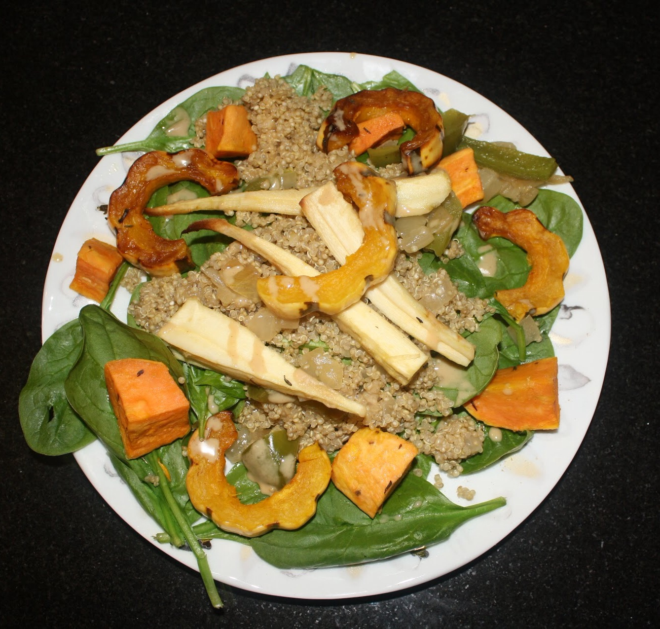My food photography has changed in the past year, thank god. Here is a bed of spinach with quinoa, roast sweet potatoes, parsnips, peppers, ions and DELICATA.