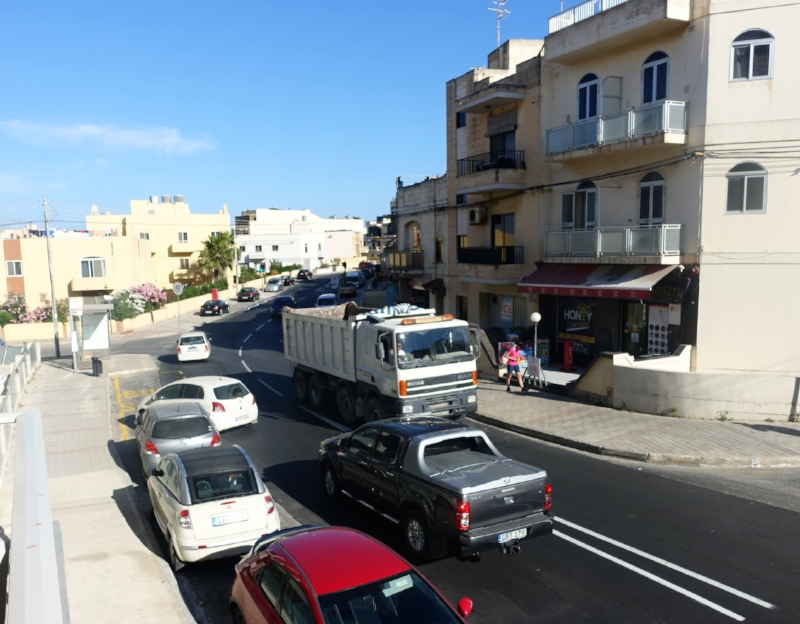 the small white car is parked in a bus zone, diagonally and with the rear sticking into the on-coming traffic. the driver is in the shop across the road.