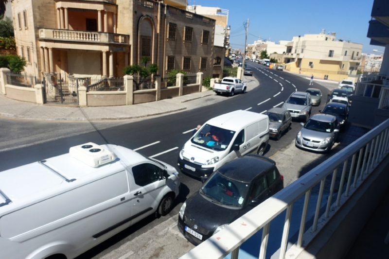 these five vehicles (actually there are 7 in all) are all double parked on a main road, including one on the opposite side to the direction of its travel