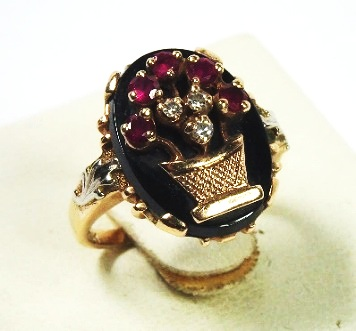 Vintage Replica - This is a modern vintage replica of an antique 'basket' ring. It contains modern round brilliant cut synthetic rubies, brilliant cut diamonds and onyx. It is of budget cast construction that potentially could have been made in the hundreds, and is let down by poor finish.