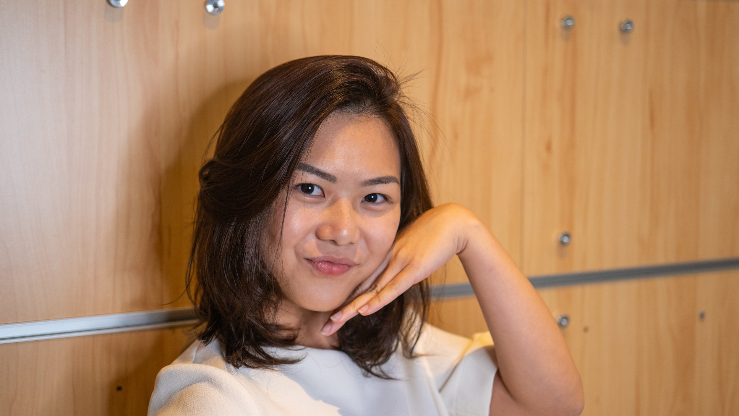 Pretty female hair model smiling and posing with hand at Du Sol Beauty Singapore located at Novena Square 2