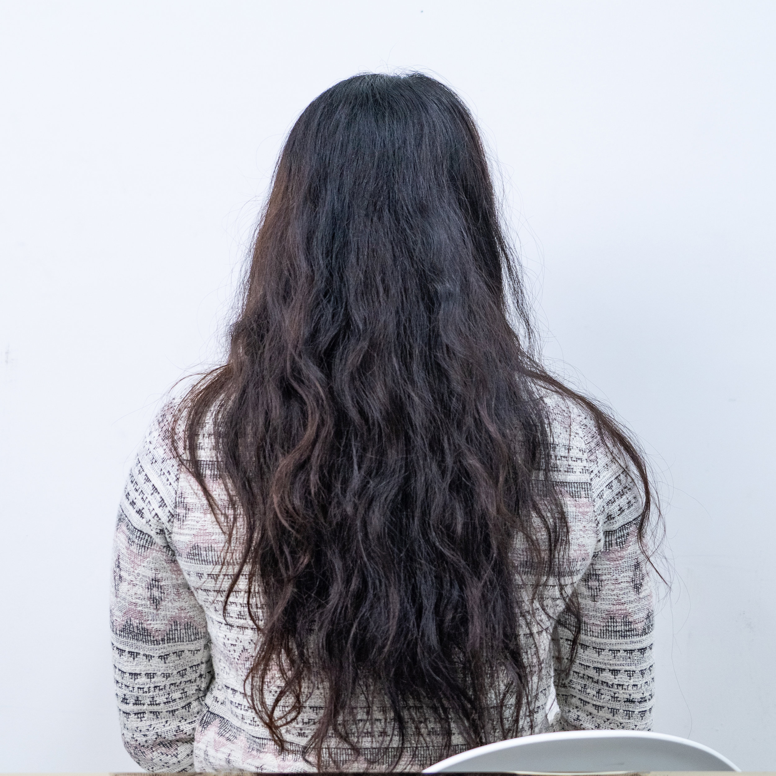 Clara, hair model's back view with natural and loose curls with a white background taken in studio of DuSol Beauty office