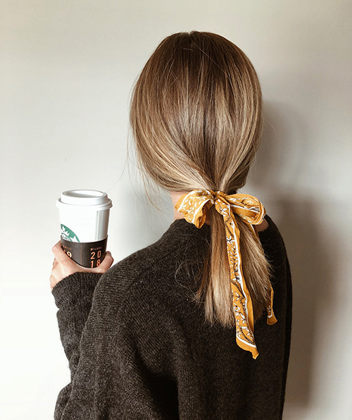 Loose ponytail tied with a ribbon can be a chic choice to look dressed up without heat styling.