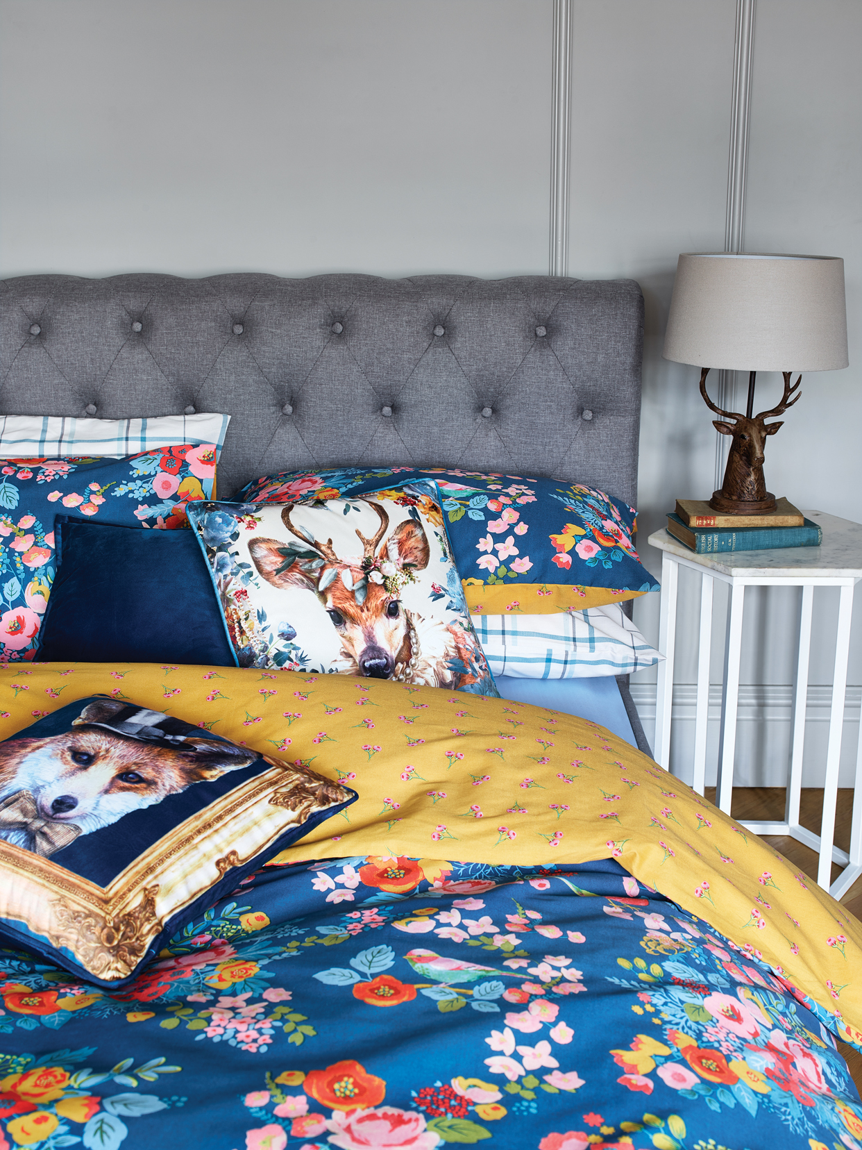 Chesterfield bed - £239, Bird and Floral double duvet set - £12, Deer cushion - £6, Blue velvet cushion - £5, Fox in a frame cushion - £6, Marble side table - £59, Stag head lamp - £27.
