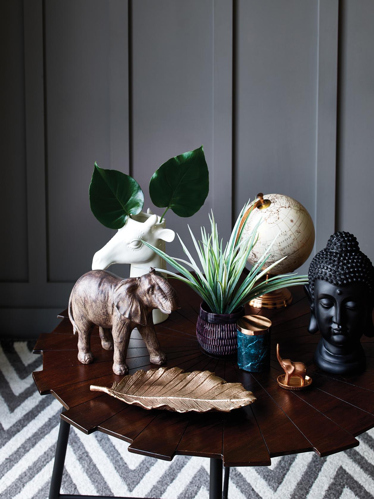 Elephant ornament - £15, Giraffe vase - £12, Copper globe - £15, Purple potted grass - £8, Marble print candle - £4, Buddha ornament - £12, Copper leaf plate - £12, Starburst coffee table - £79, Homemaker grey chevron rug - £60.