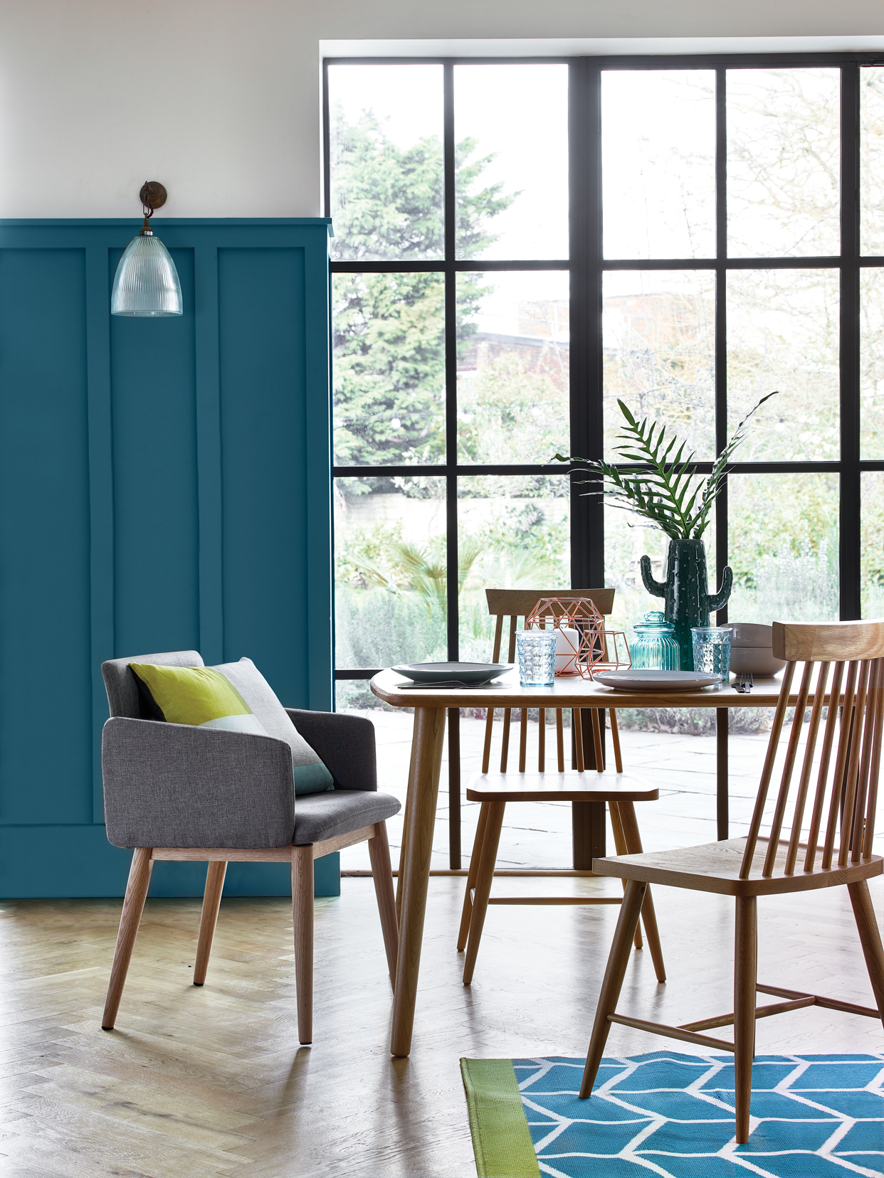 Retro upholstered grey chair, £59, Scandi Geo cushion - £6, Idris solid oak table - £259, Idris solid oak chairs - £99, Blushed pink 12 piece dinner set - £18, Jade dinner plates (set of 4) - £6, Copper wire candle holder - £10, Copper wire tealight holder - £3, Cactus vase - £12, Textured glass - £1.50, Satin Ripley 16 piece cutlery set - £15, Homemaker teal chevron rug - £40.