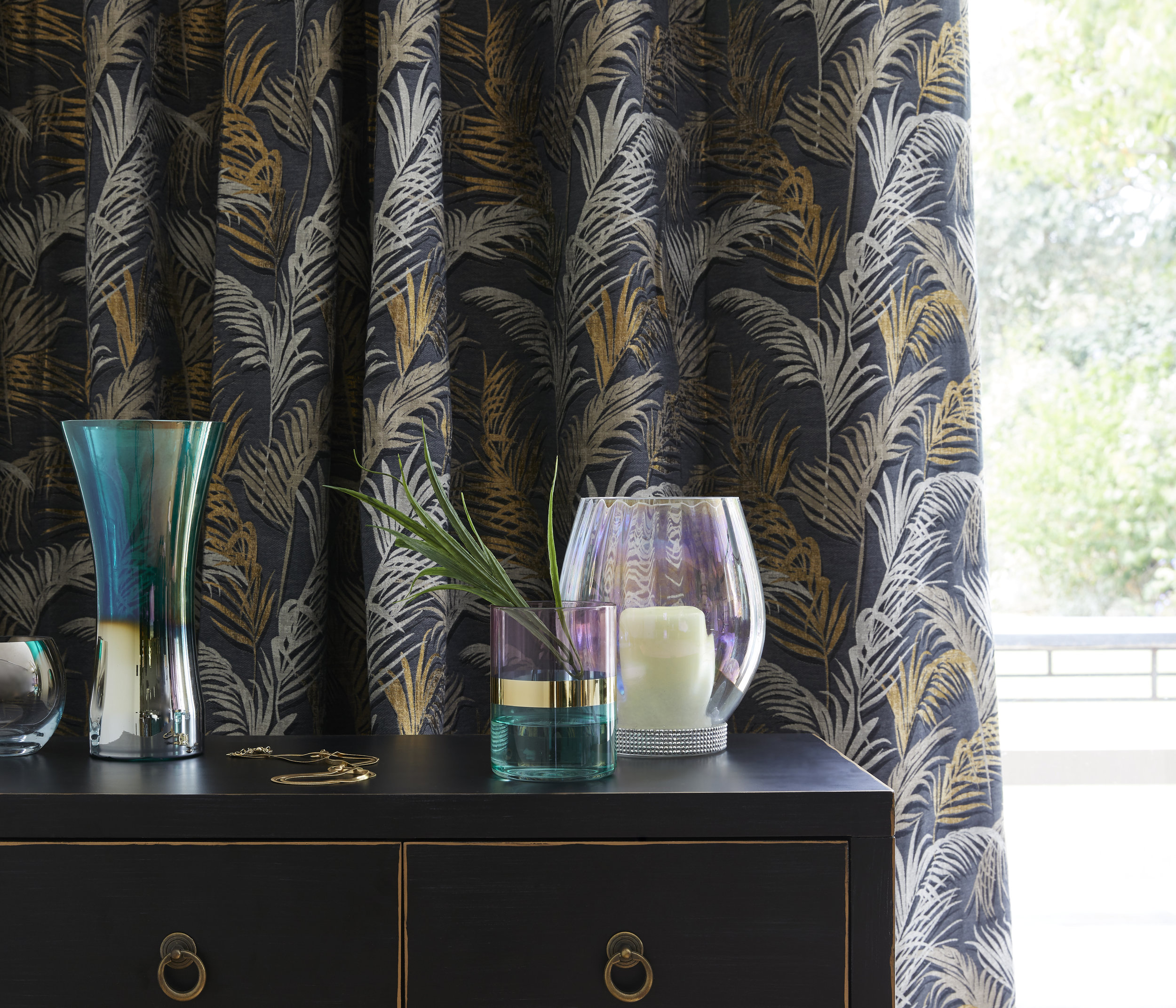 Hanna small sideboard, £149  Palm eyelet curtains, from £55  Lustre glass tealight holder, £7  Teal lustre flare vase, £12  Two-tone glass tealight holder, £6  Lustre glass hurricane with diamanté base, £16  Photo: Dunelm