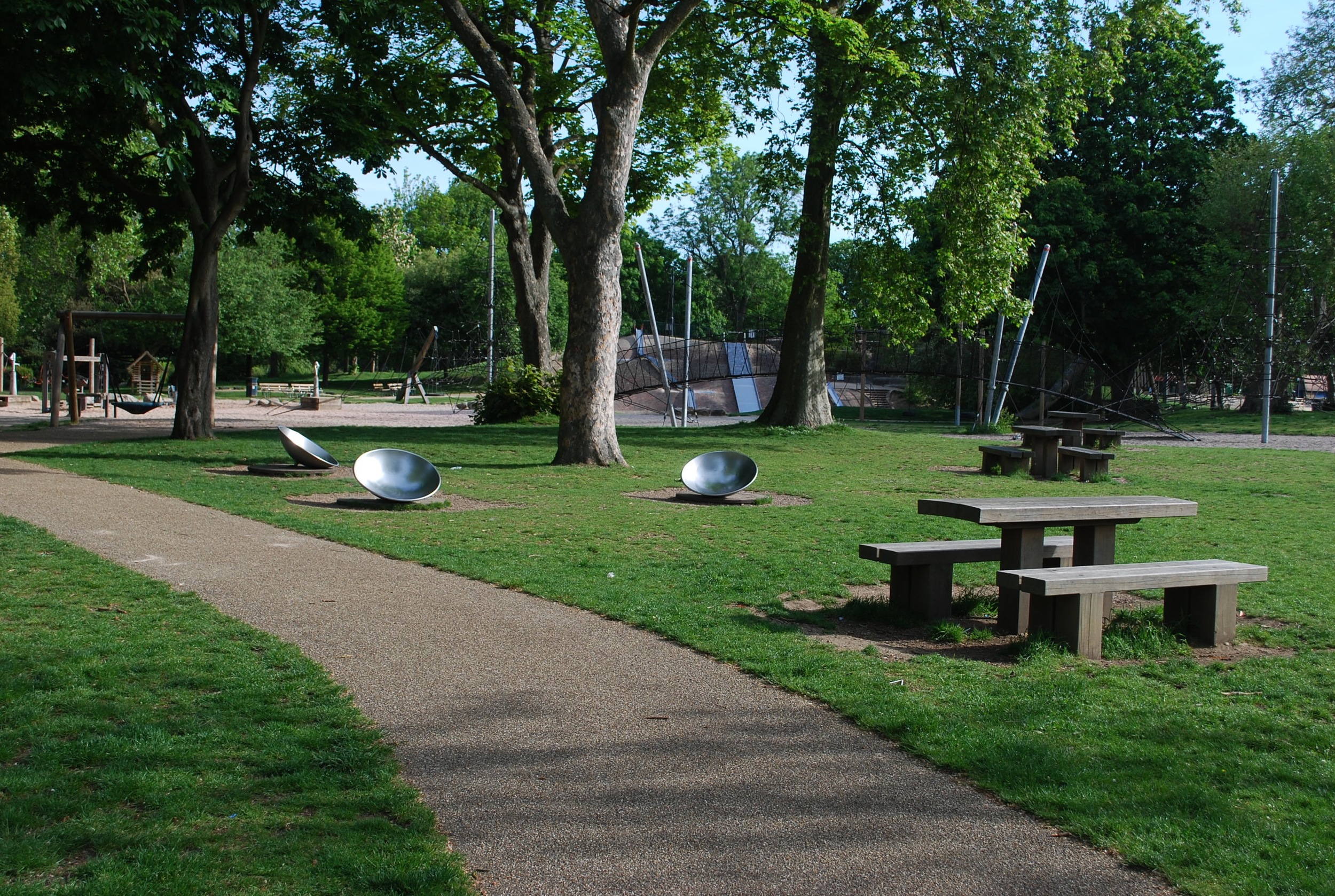 Tables and benches at Pools Playground, Victoria Park, are within sight of the playground, but not interfering with play flow