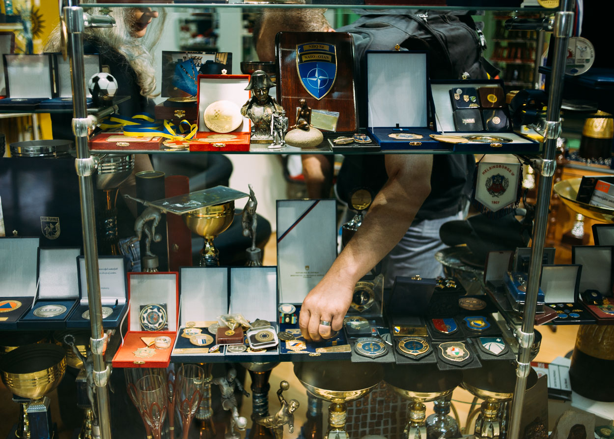 Andrej inspects replica medals at a trophy shop. Also shown in the window are replica police badges, similar to the one on Andrej's hip.