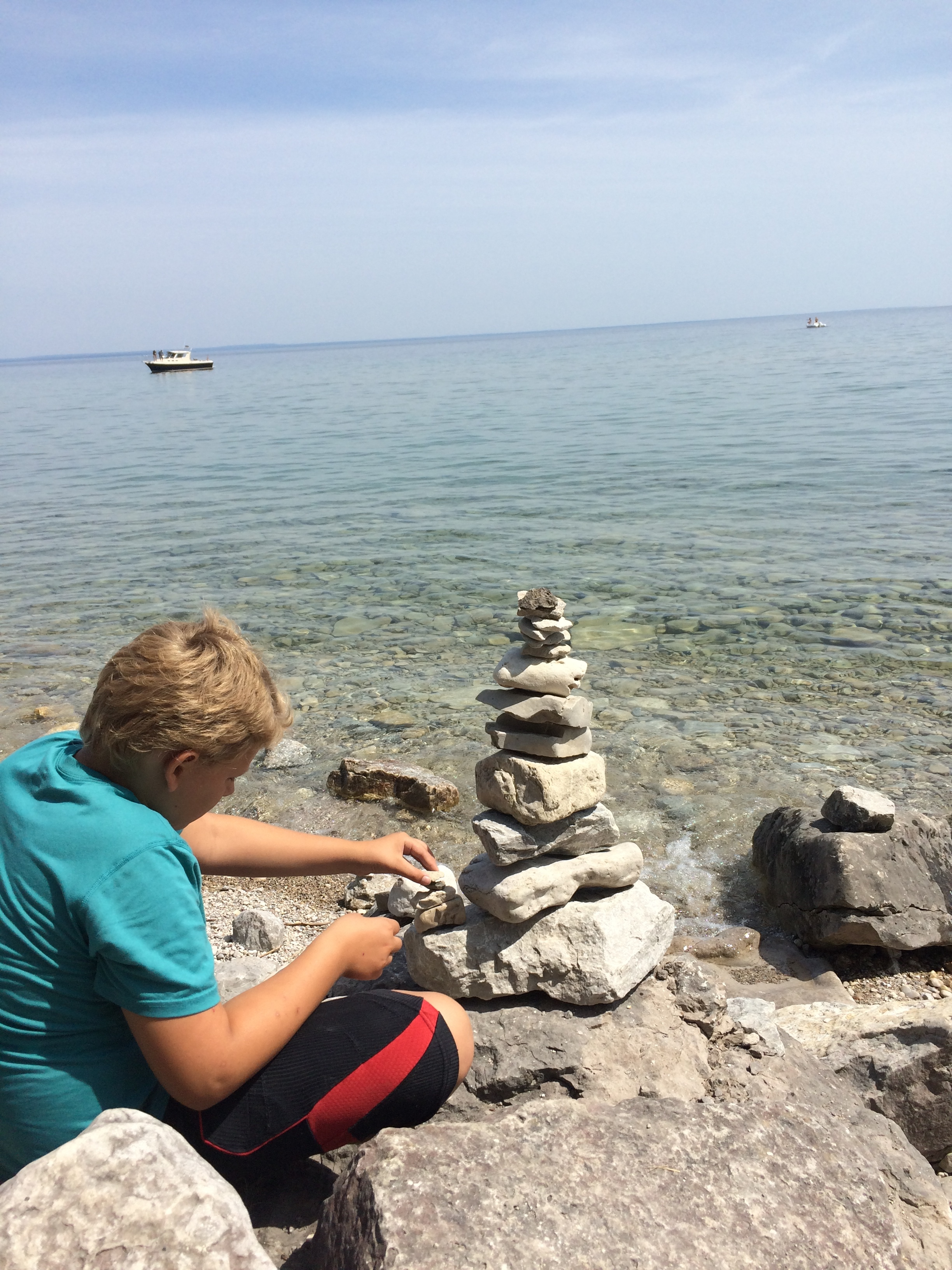 Cairn building on the shores of Lake Michigan can be an hours-long pastime for this guy who takes the world in deeply.